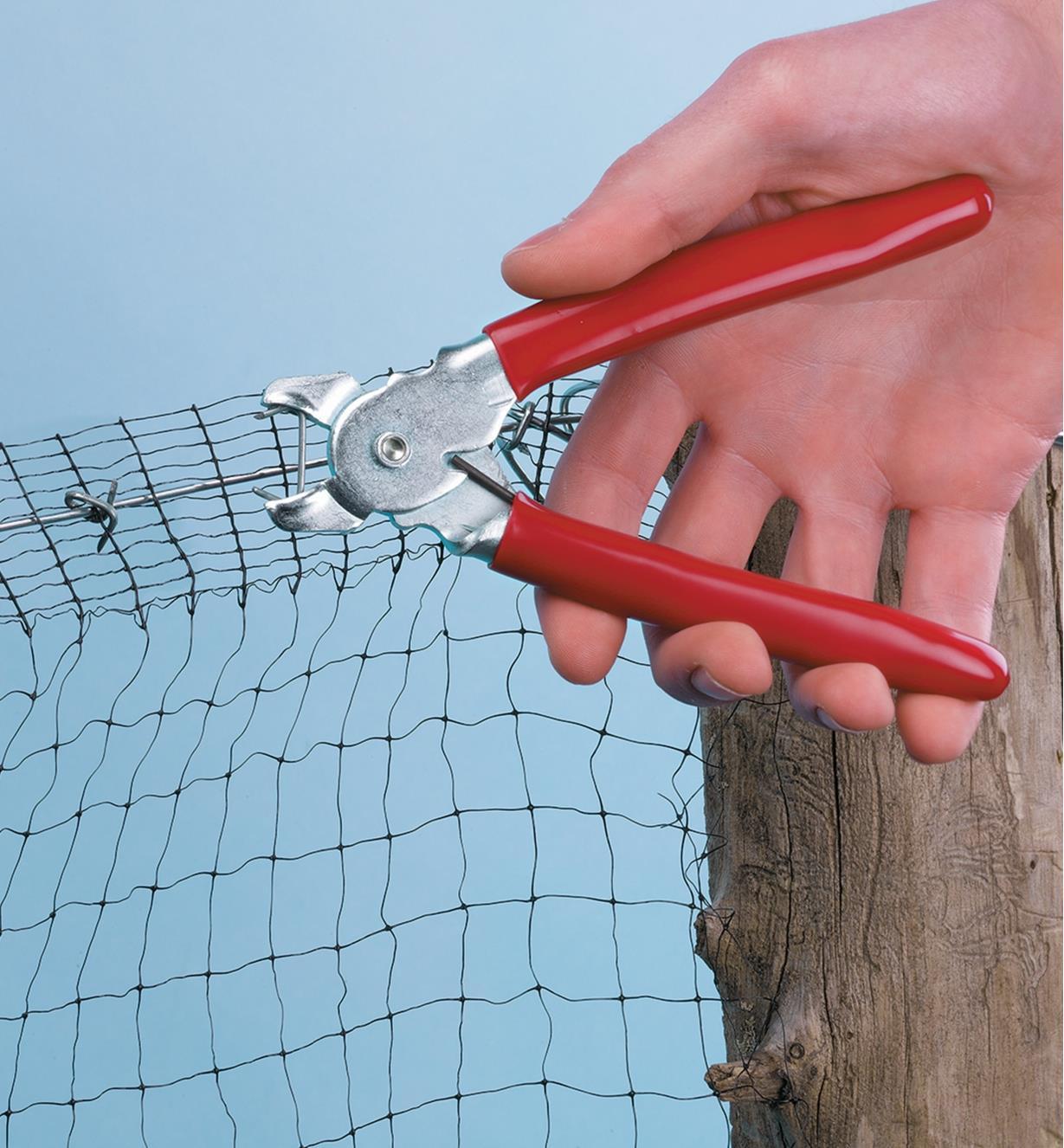 Personne réparant une clôture à l'aide d'un anneau et des pinces pour anneaux ouverts