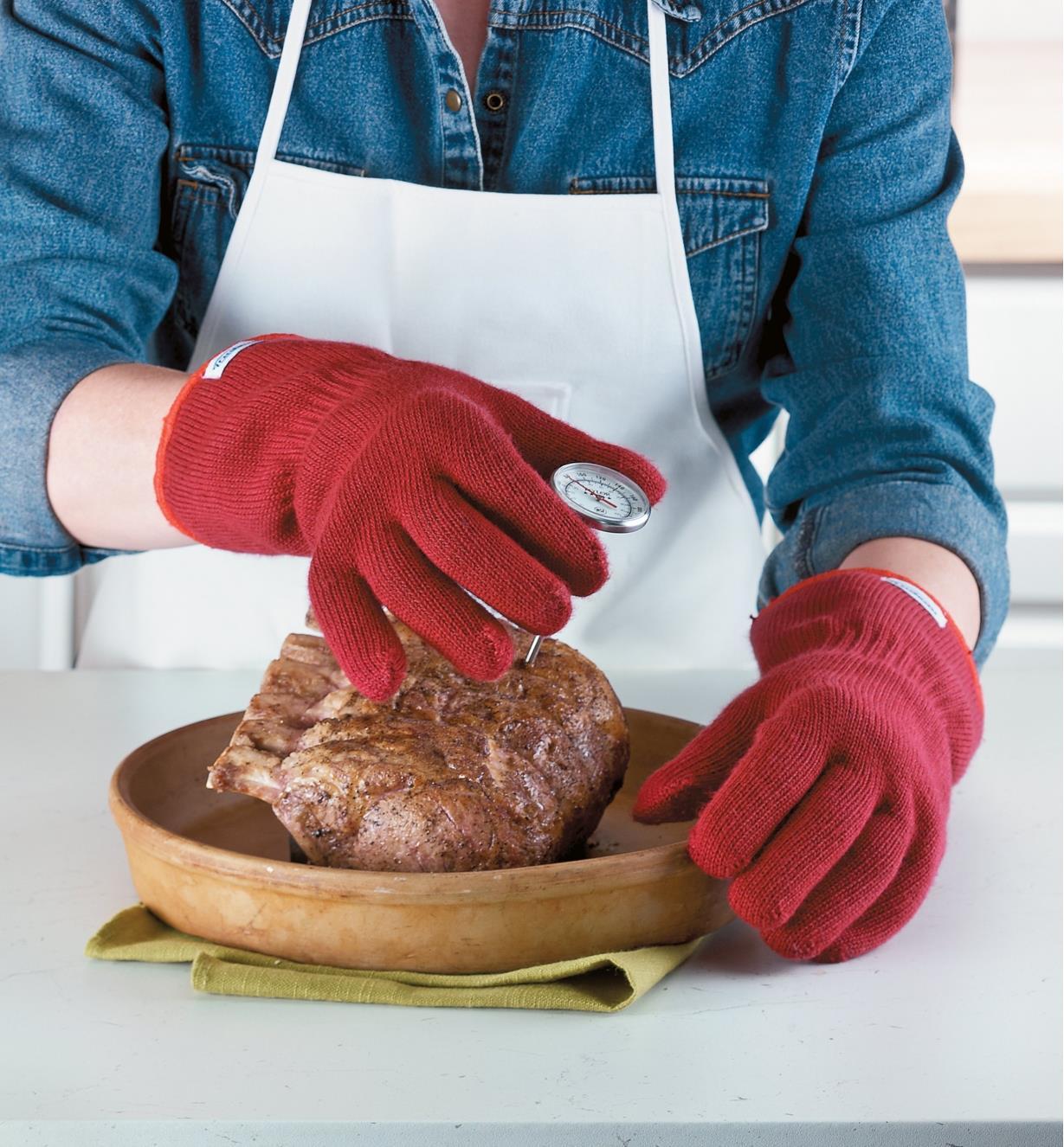 Mains protégées par les gants de cuisine lors du contrôle de la température d'une viande fraîchement cuite