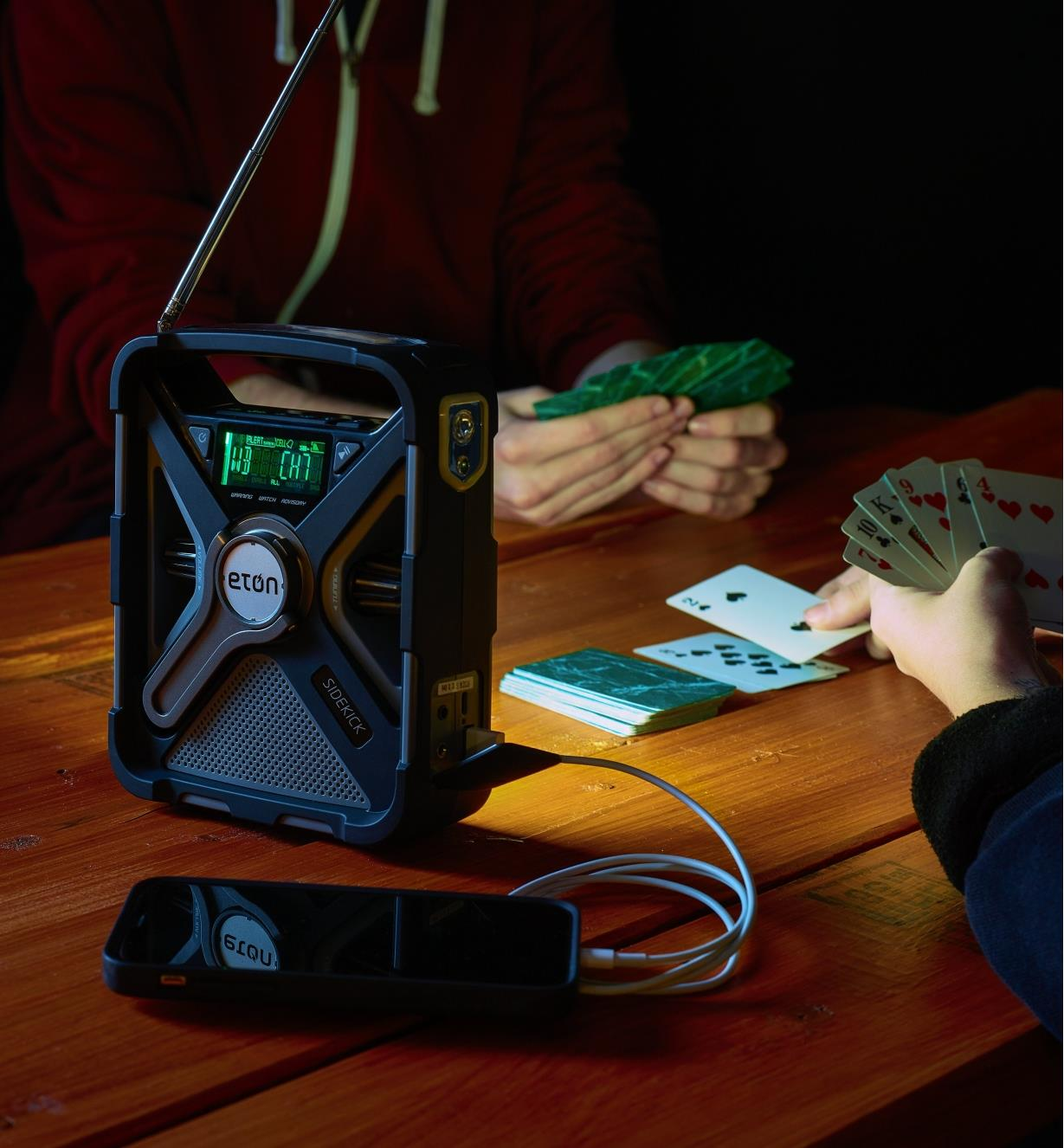 Using the light on the Eton emergency weather radio to play cards while the radio charges a cell phone
