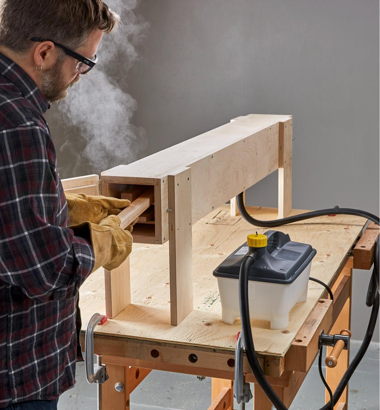 Placing a wooden workpiece inside a steam box connected to an Earlex steam generator