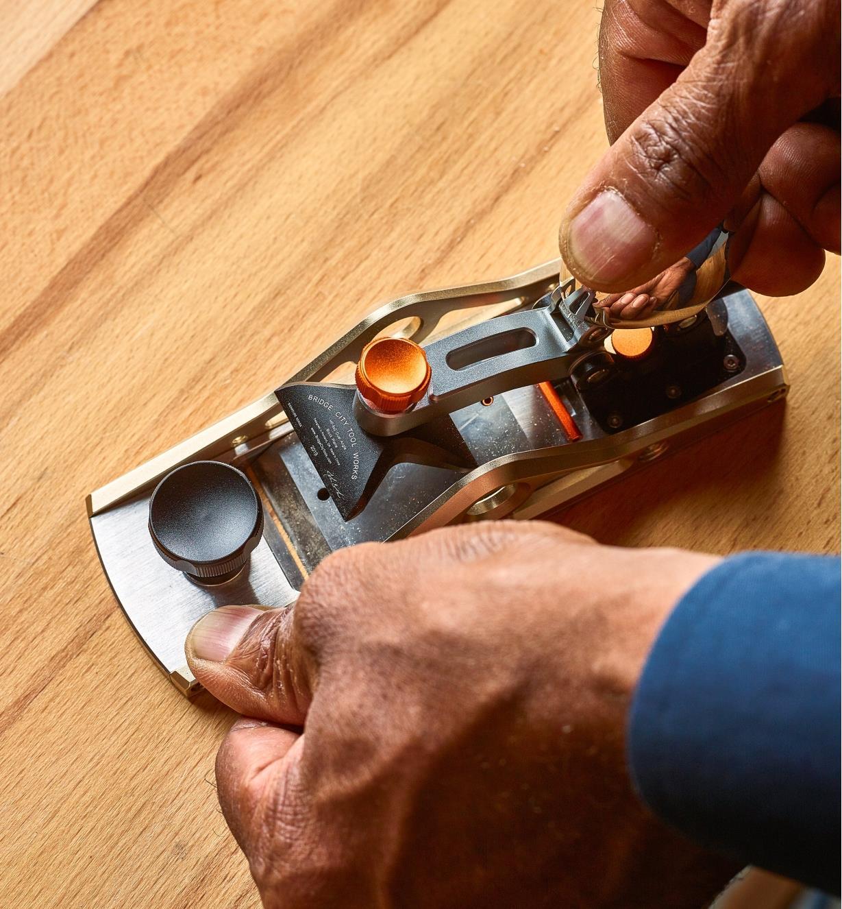 Personne relevant le levier du mécanisme de blocage pour changer la lame d'un rabot de coupe à double tranchant