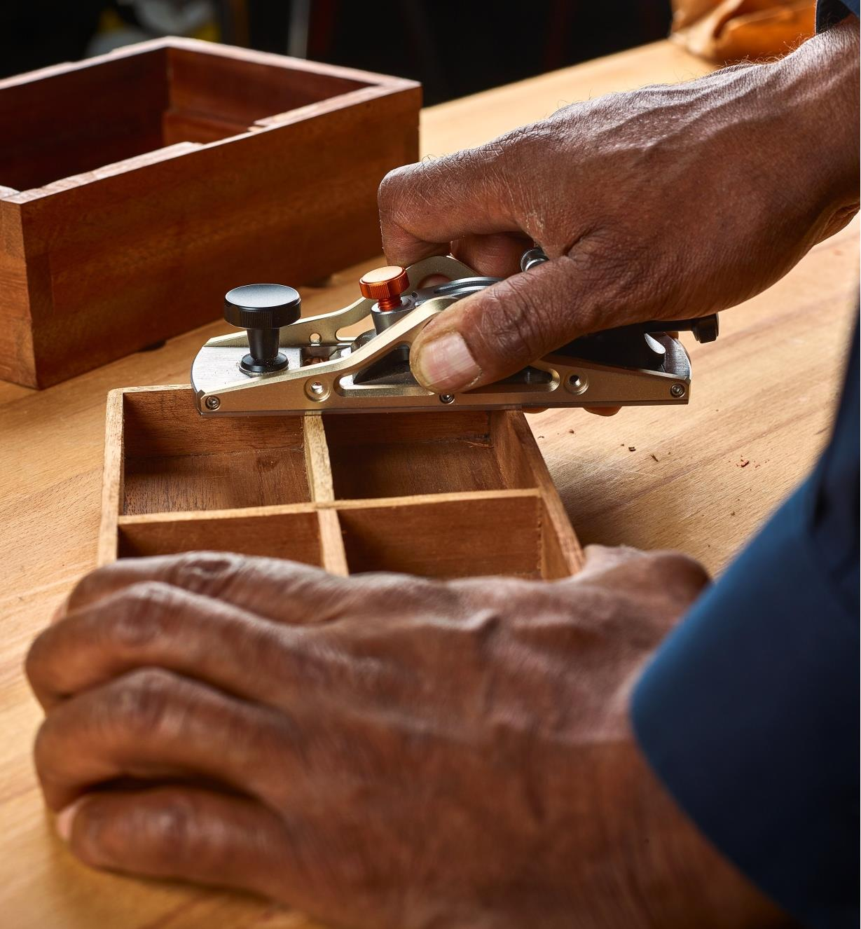 A woodworker uses a dual-angle block plane to level the walls of a wooden box