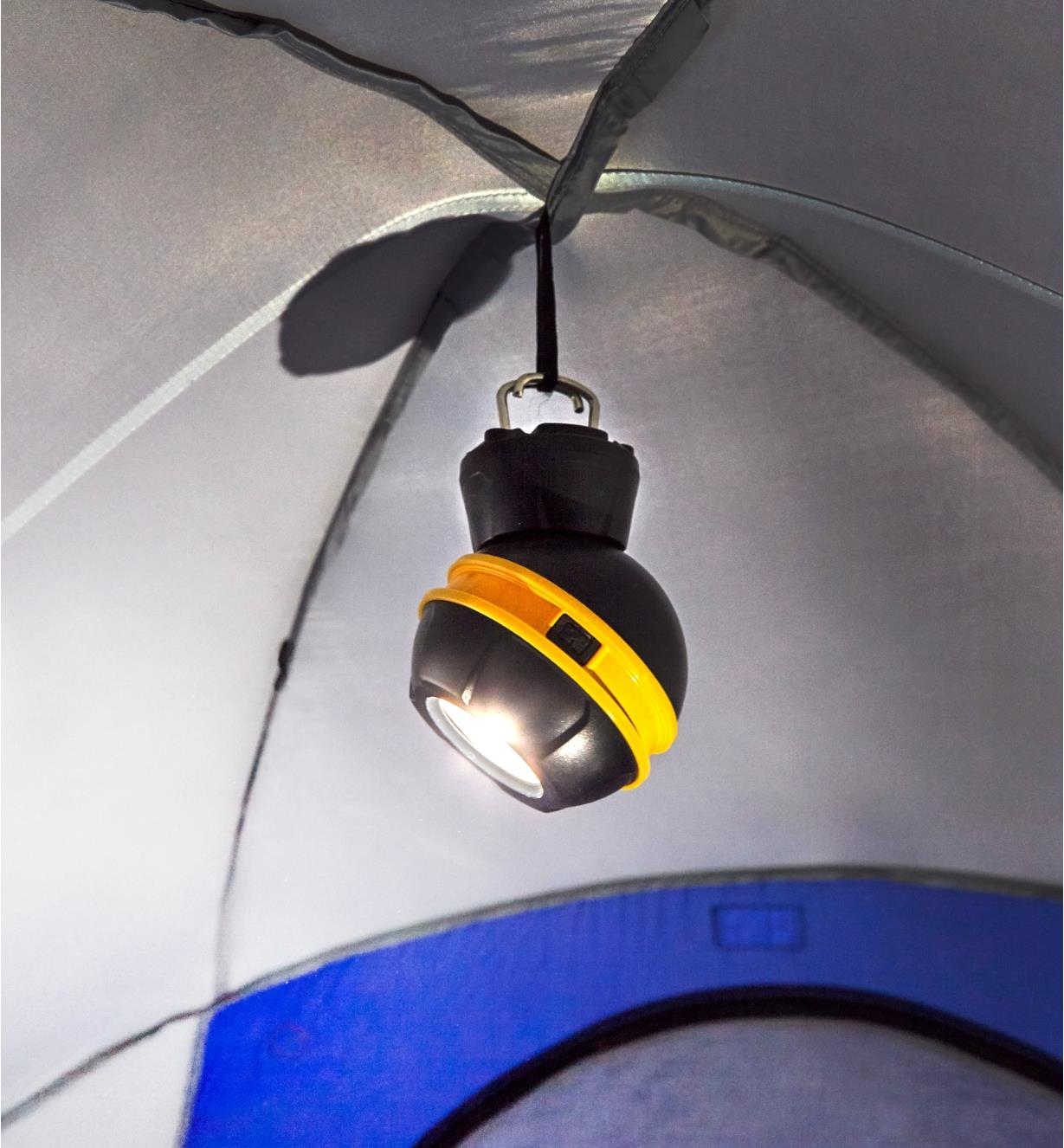 A rechargeable orb light hung from the ceiling of a tent using fold-out hooks built into the base