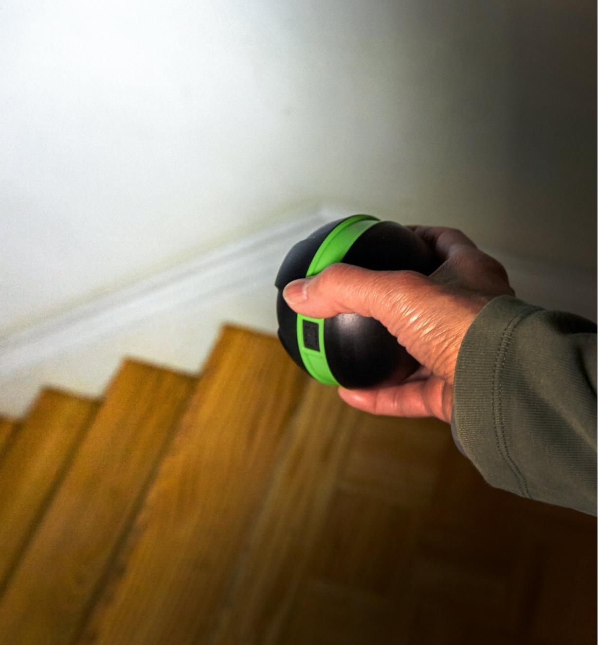 A battery-powered orb light used without the base, aimed by hand to illuminate a flight of stairs
