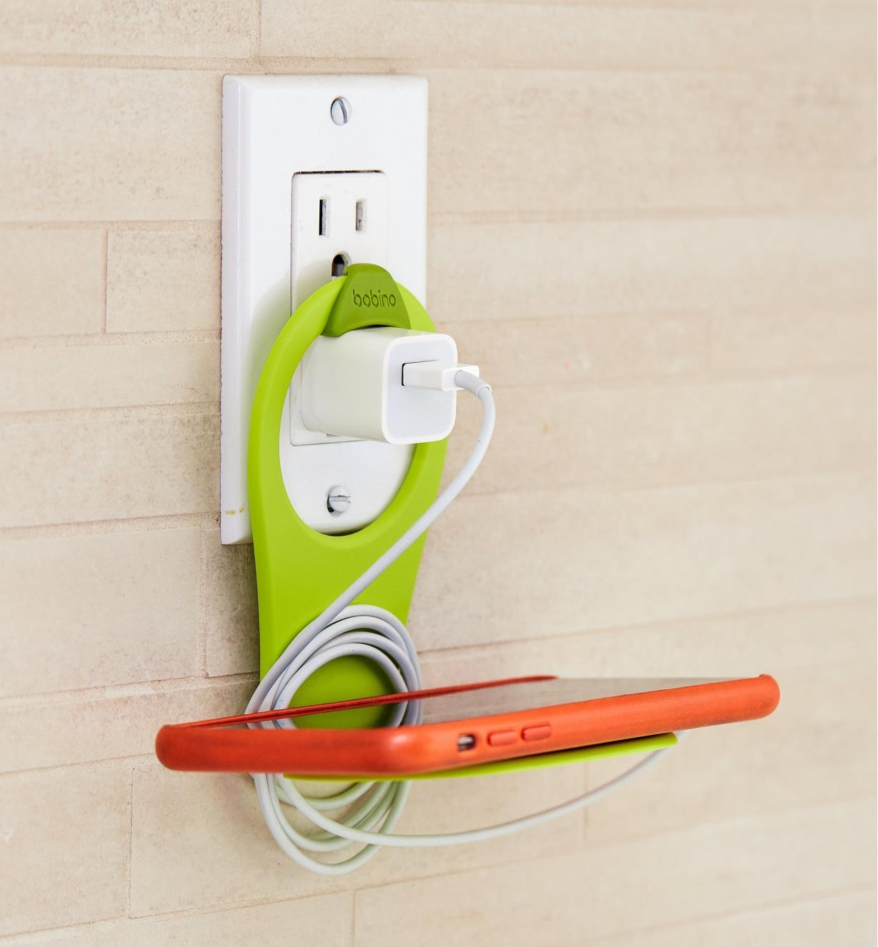 Lime Folding Phone Holder hooked over a charger in an outlet, holding a cell phone
