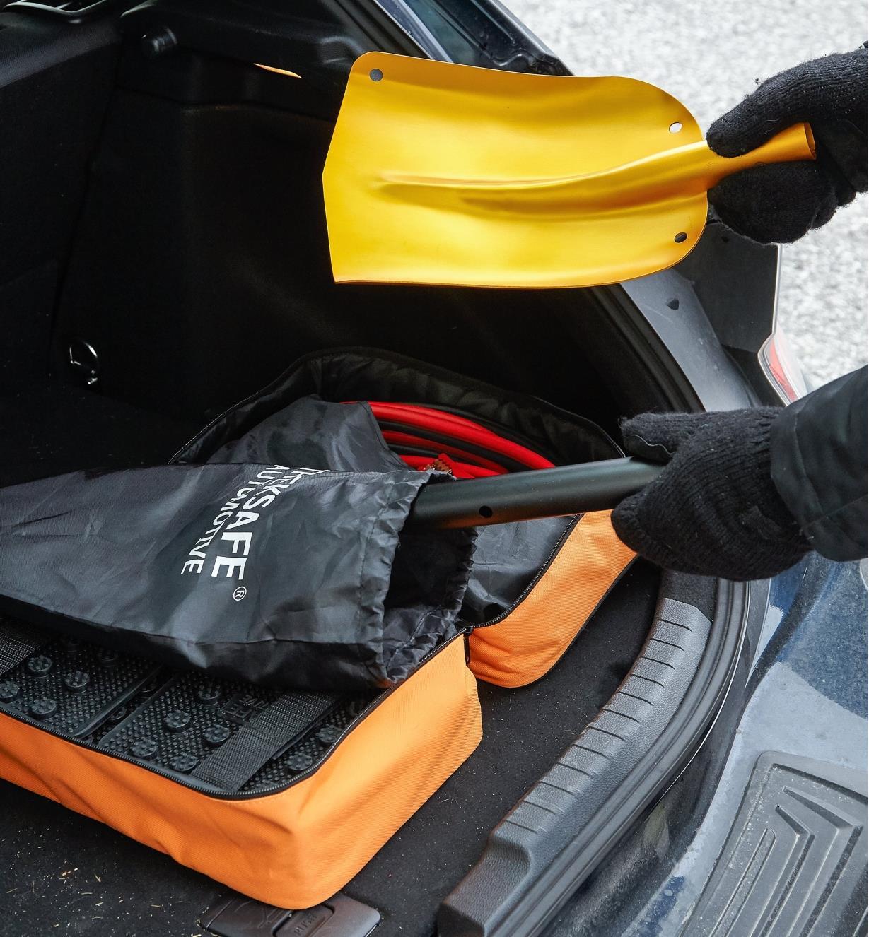 Personne retirant les pièces de la pelle démontable d'une trousse d'urgence pour véhicule dans le coffre d'une voiture