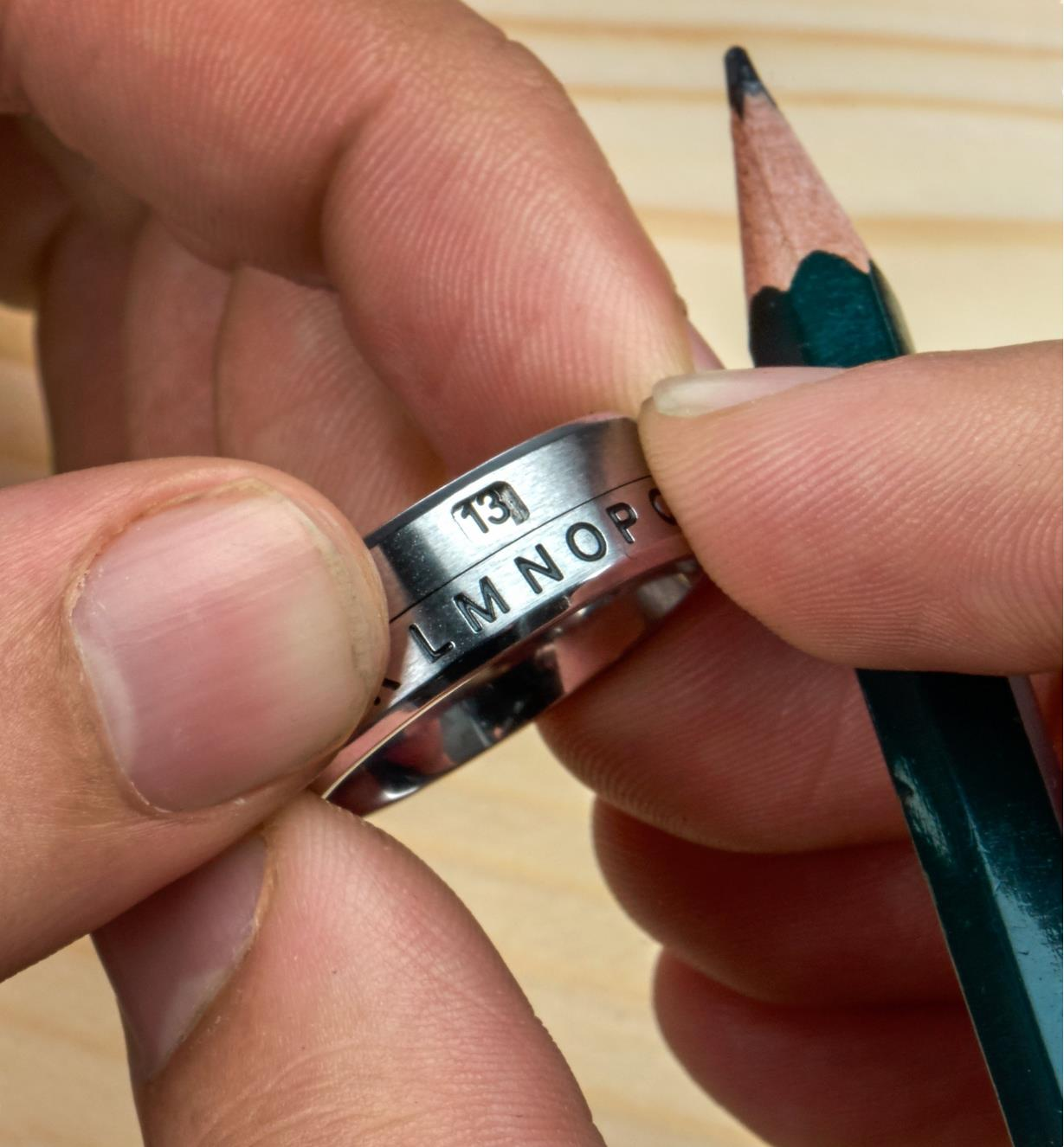 The rotating band on a secret decoder ring is turned to reveal the number associated with a letter