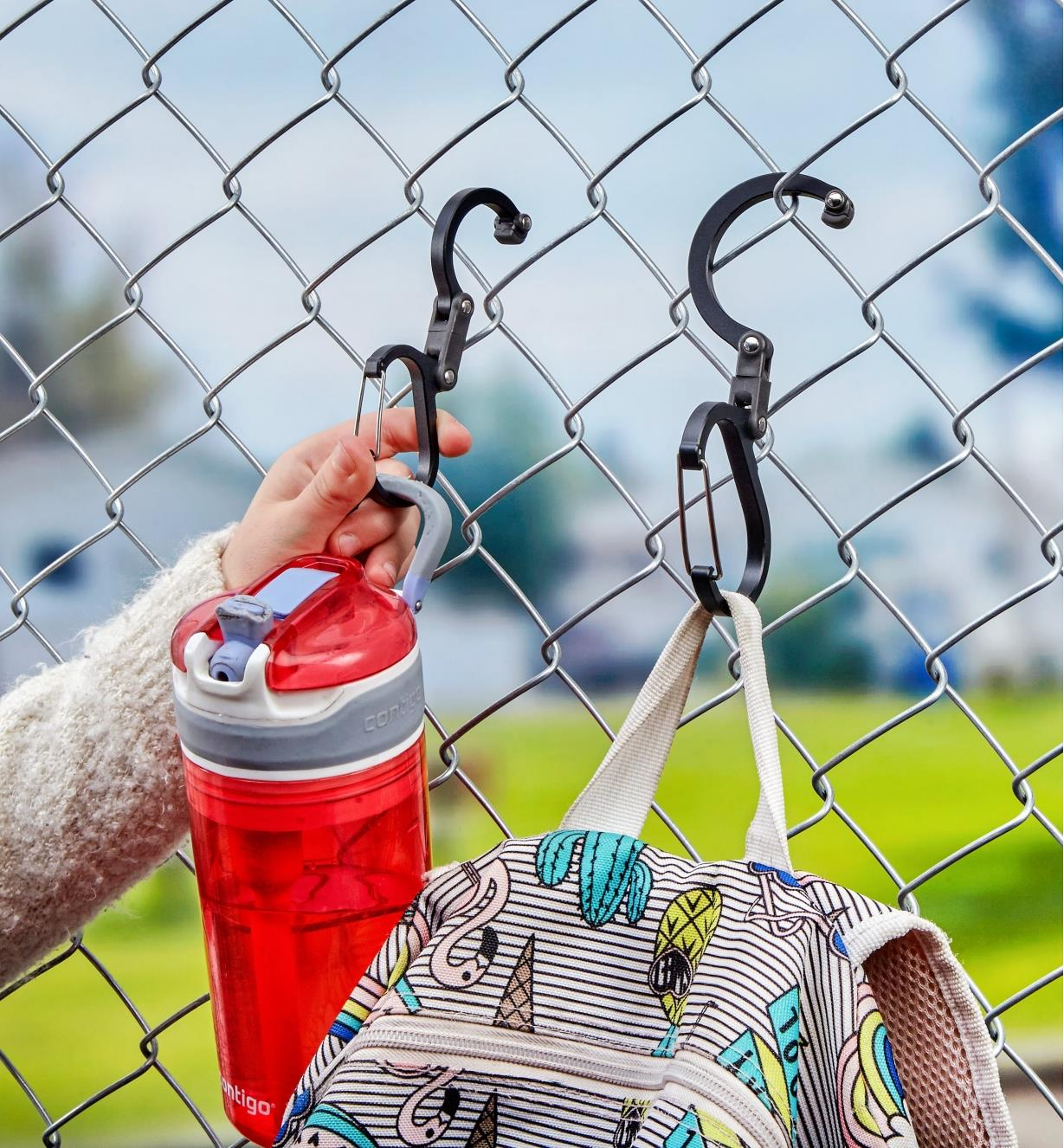 Two Heroclip carabiners used to hang a child's water bottle and backpack on a schoolyard fence