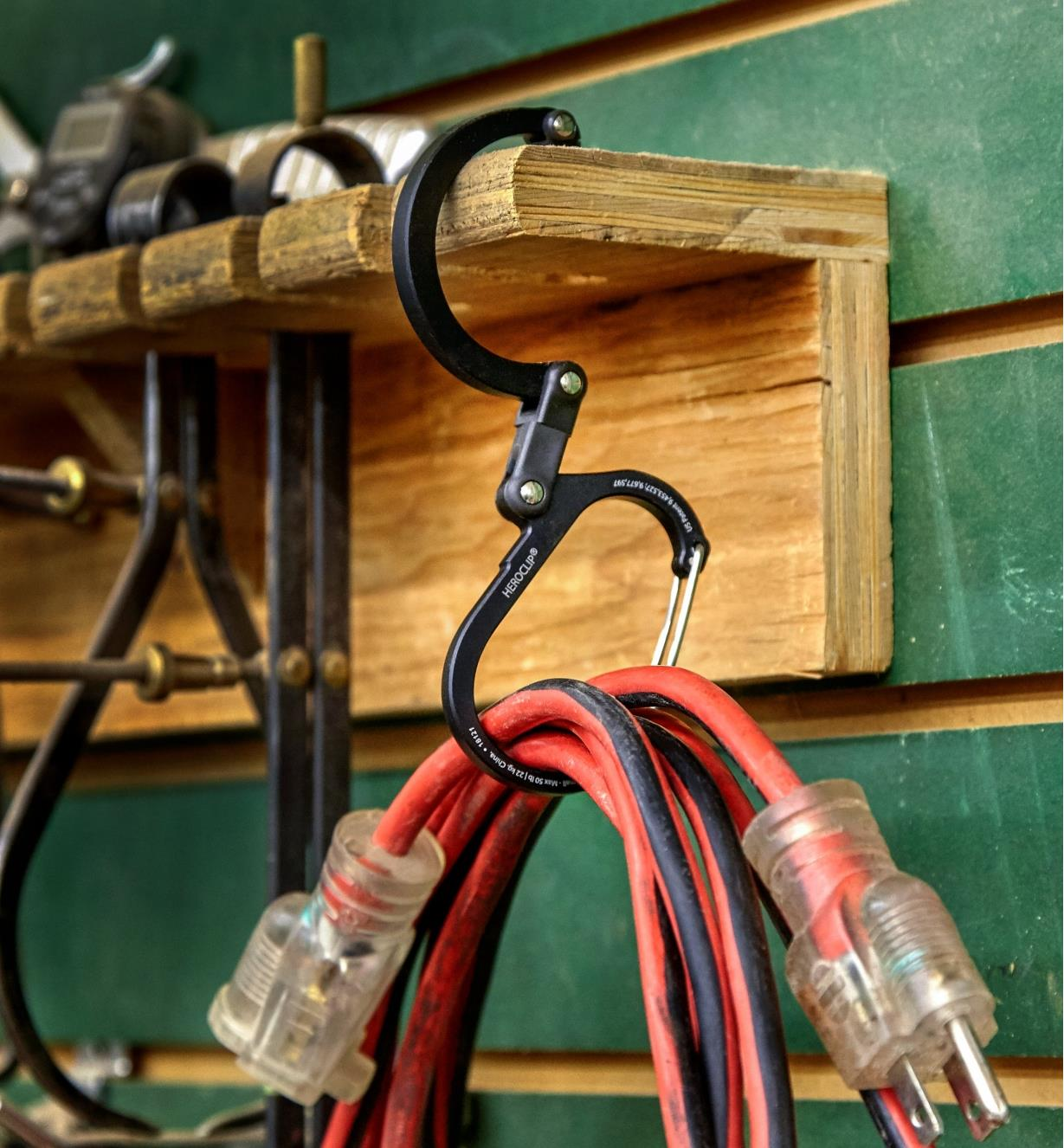 A Heroclip carabiner used to hang a coiled extension cord from a shelf in a workshop
