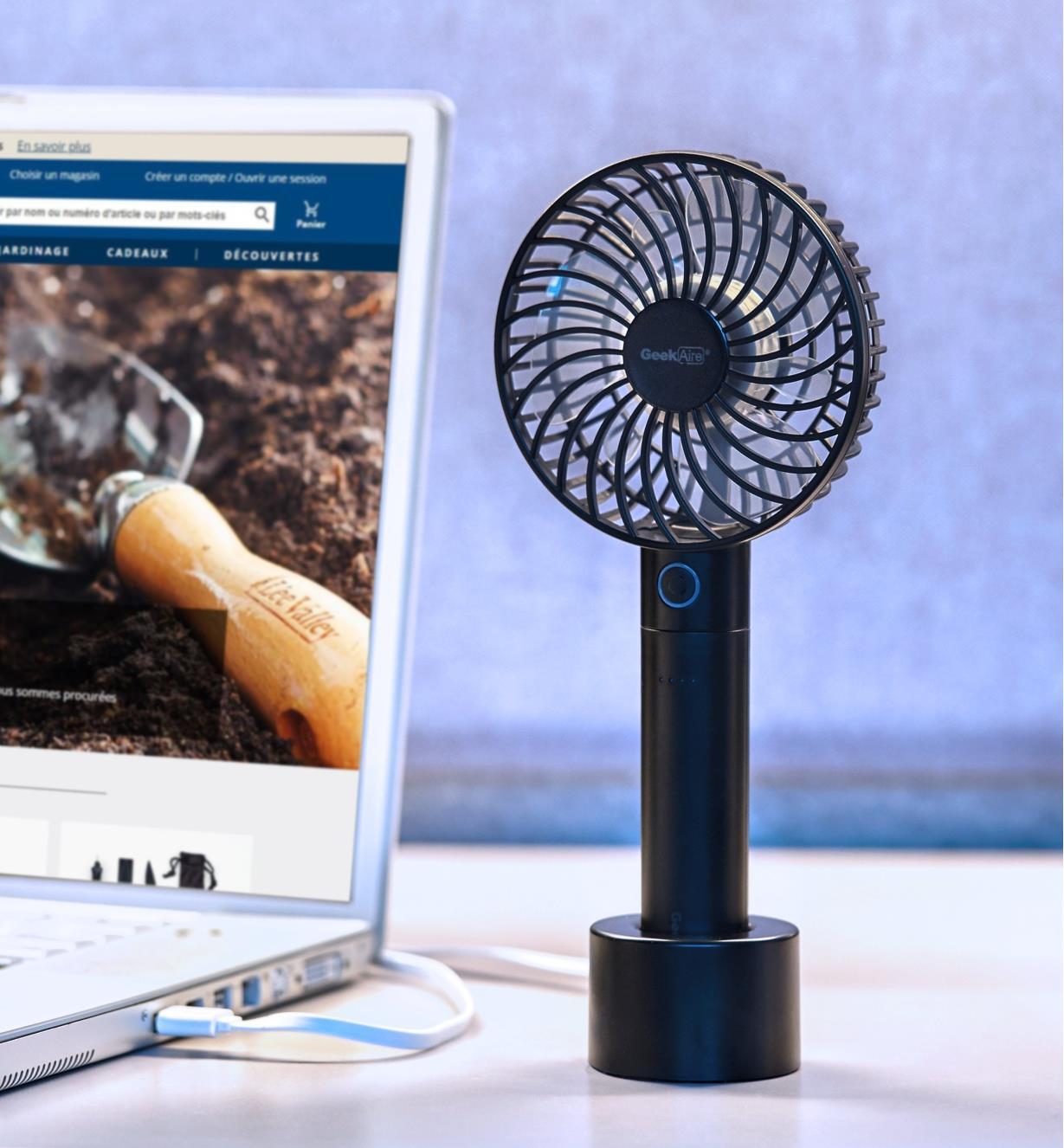 Mini ventilateur turbo rechargeable sur sa base antidérapante à côté d'un ordinateur portable sur un bureau
