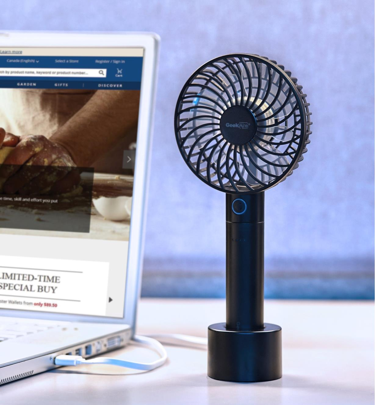 A rechargeable portable turbo fan standing on its non-slip base beside a laptop computer on a desk