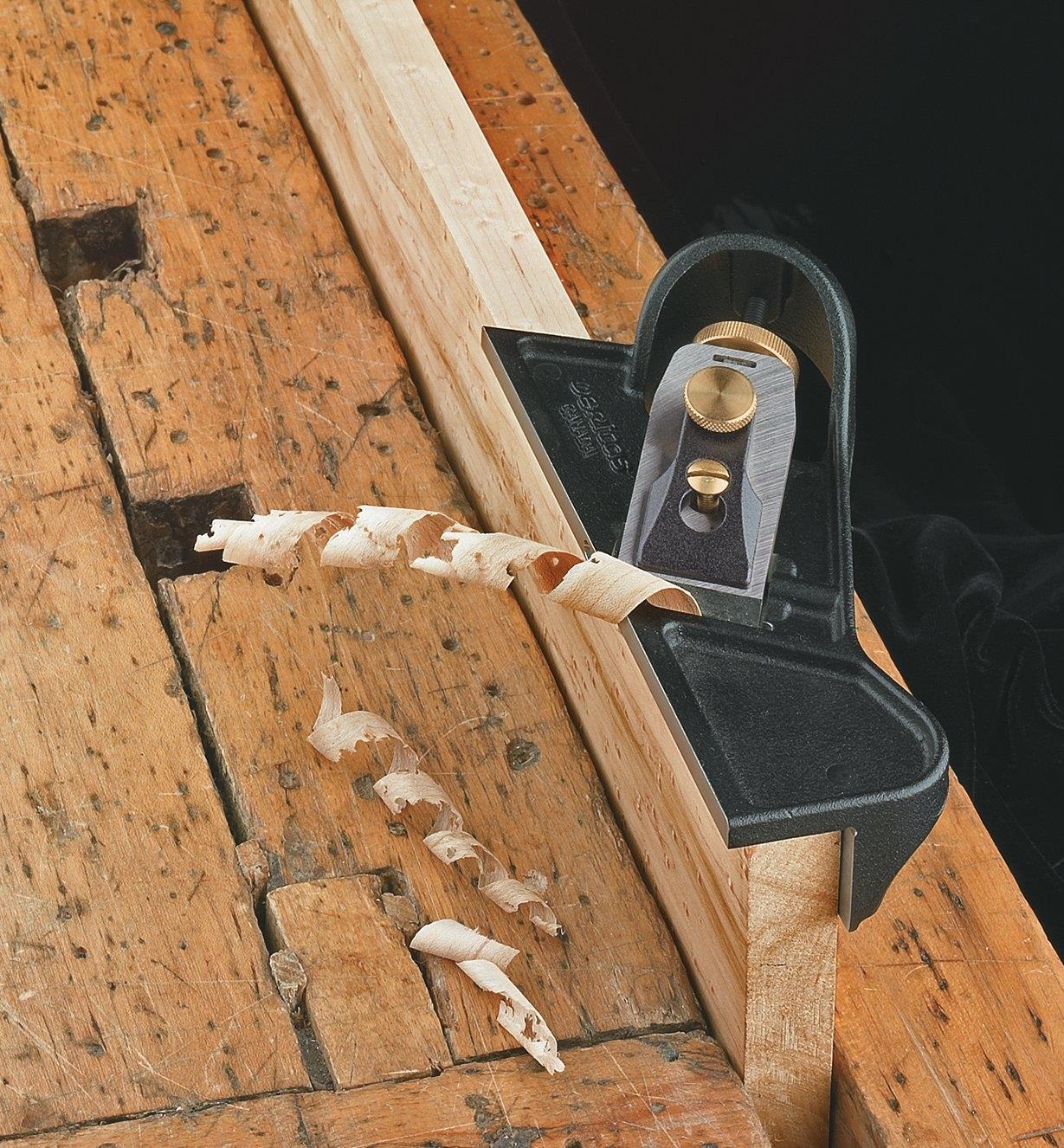 Rabot à épaulement à droite sur une planche en bois