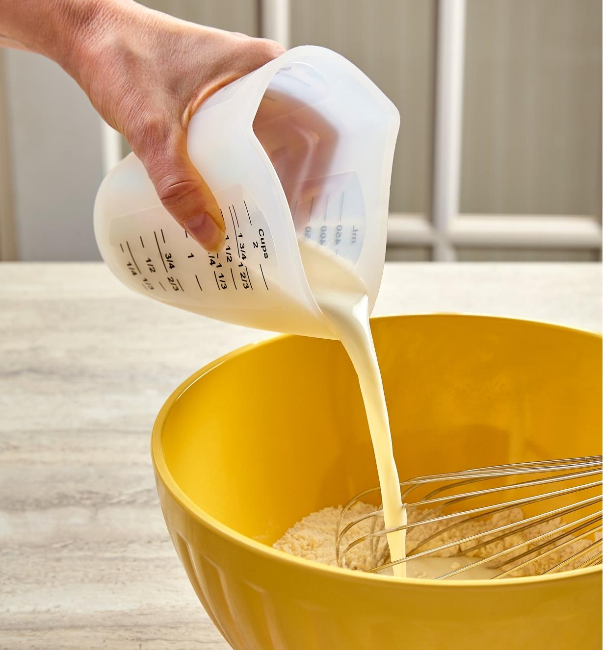 Squeezing the sides of the flexible silicone measuring cup narrows the spout, controlling the pour of milk into a mixing bowl