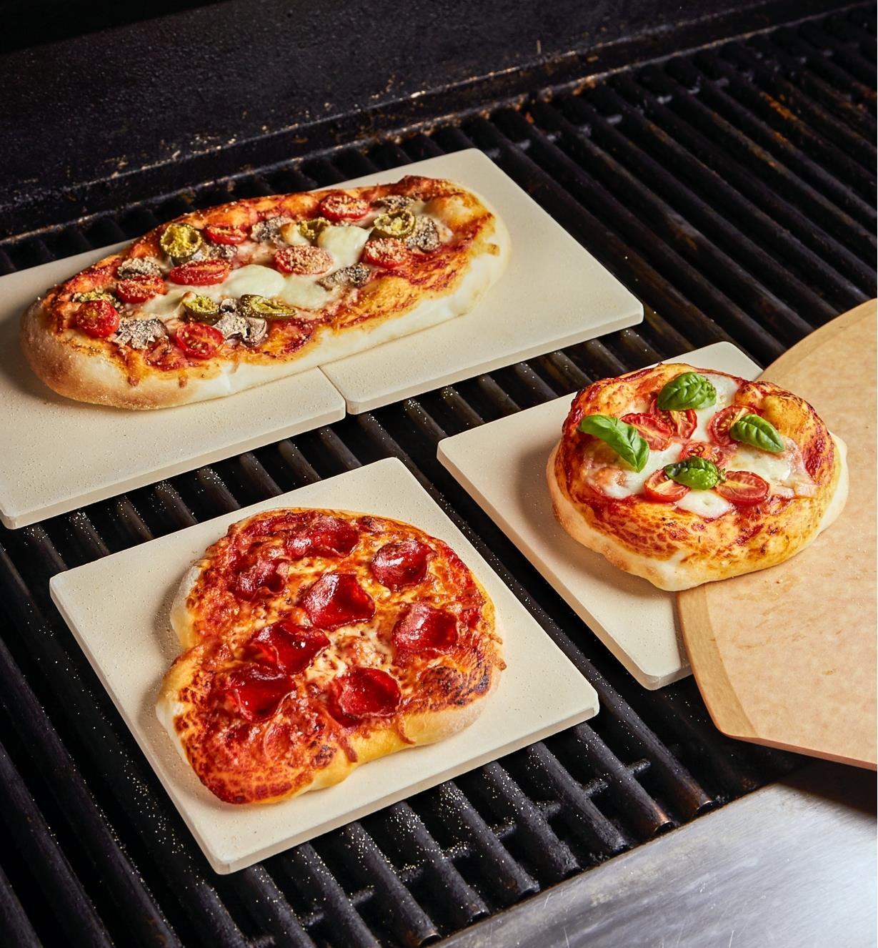 Homemade pizzas cooking on barbecue pizza stones in a barbecue