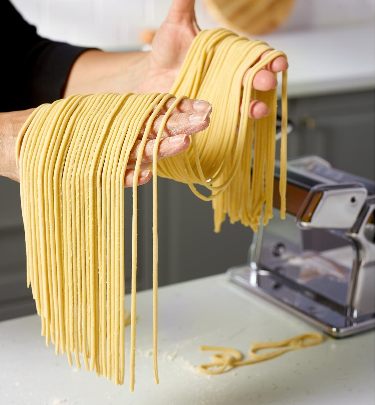 A cook gathers bigoli noodles made using a Marcato pasta machine with the bigoli cutter attachment