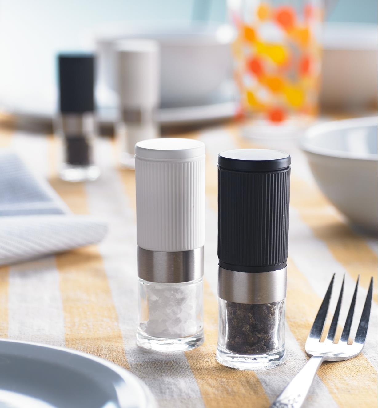 Mini salt and pepper grinders on a dining table