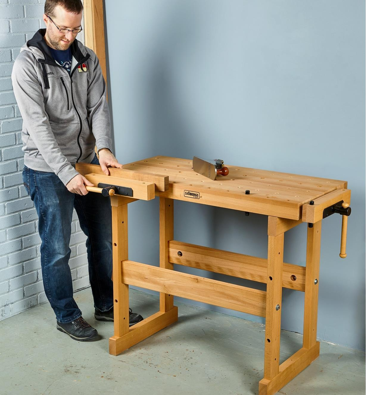 A man securing a block of wood in the front vise of the Sjöbergs apartment workbench