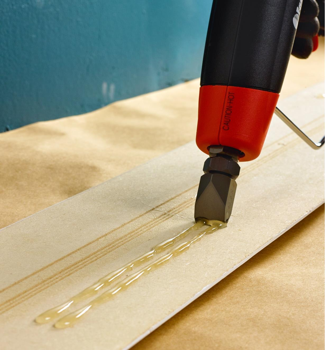 Installing trim using a double-flow nozzle on a FastenMaster Pro Hot-Melt Gun to glue it in place