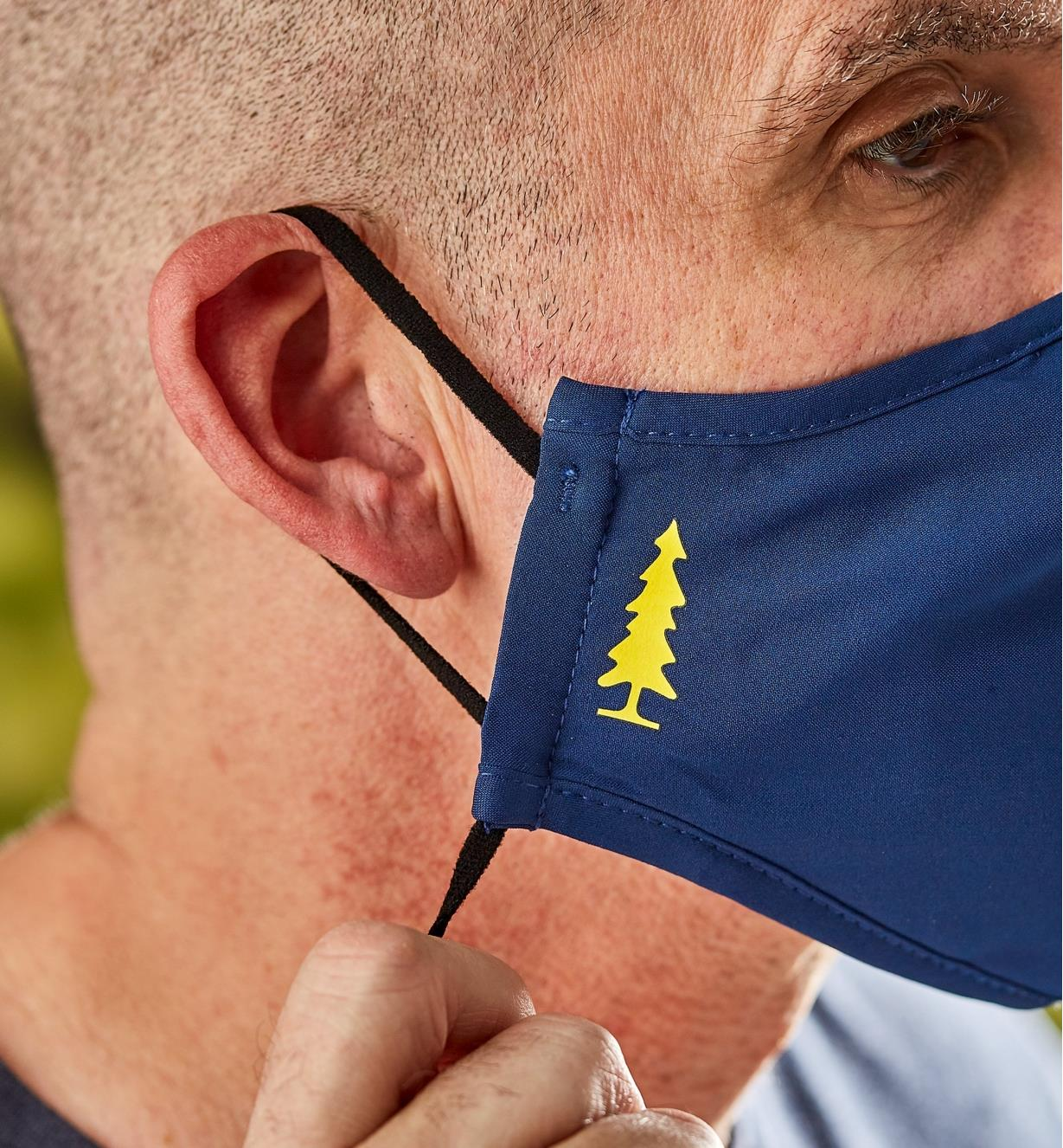 A side view of a man wearing a Lee Valley face mask, showing the adjustable ear band