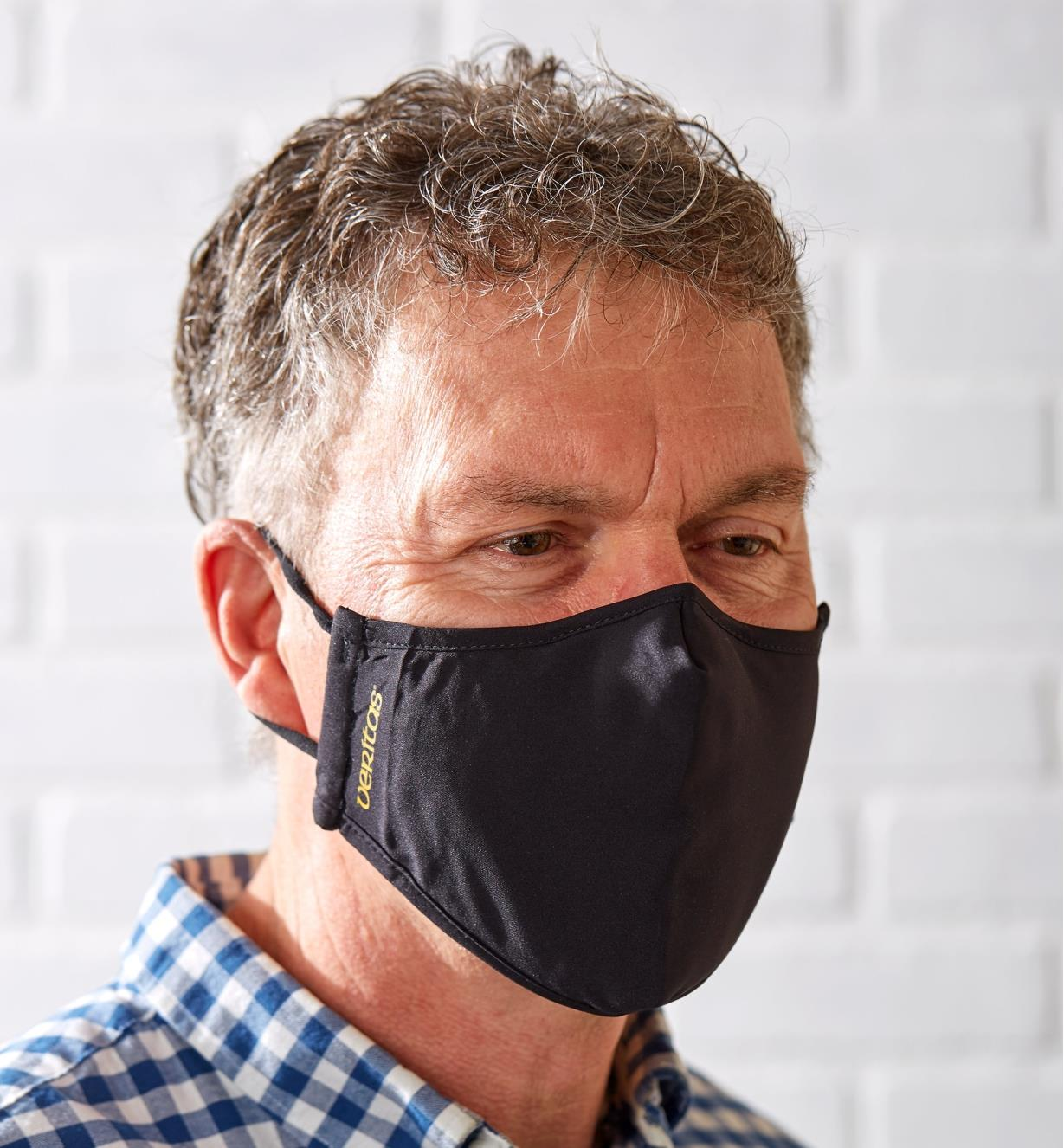 A front view of a man wearing a Veritas face mask