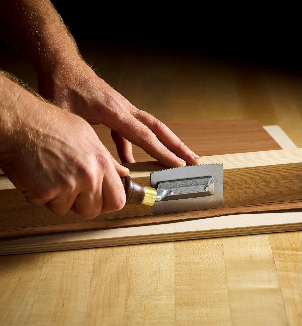 A woodworker uses a Pax veneer saw to make a precise cut in a sheet of wooden veneer