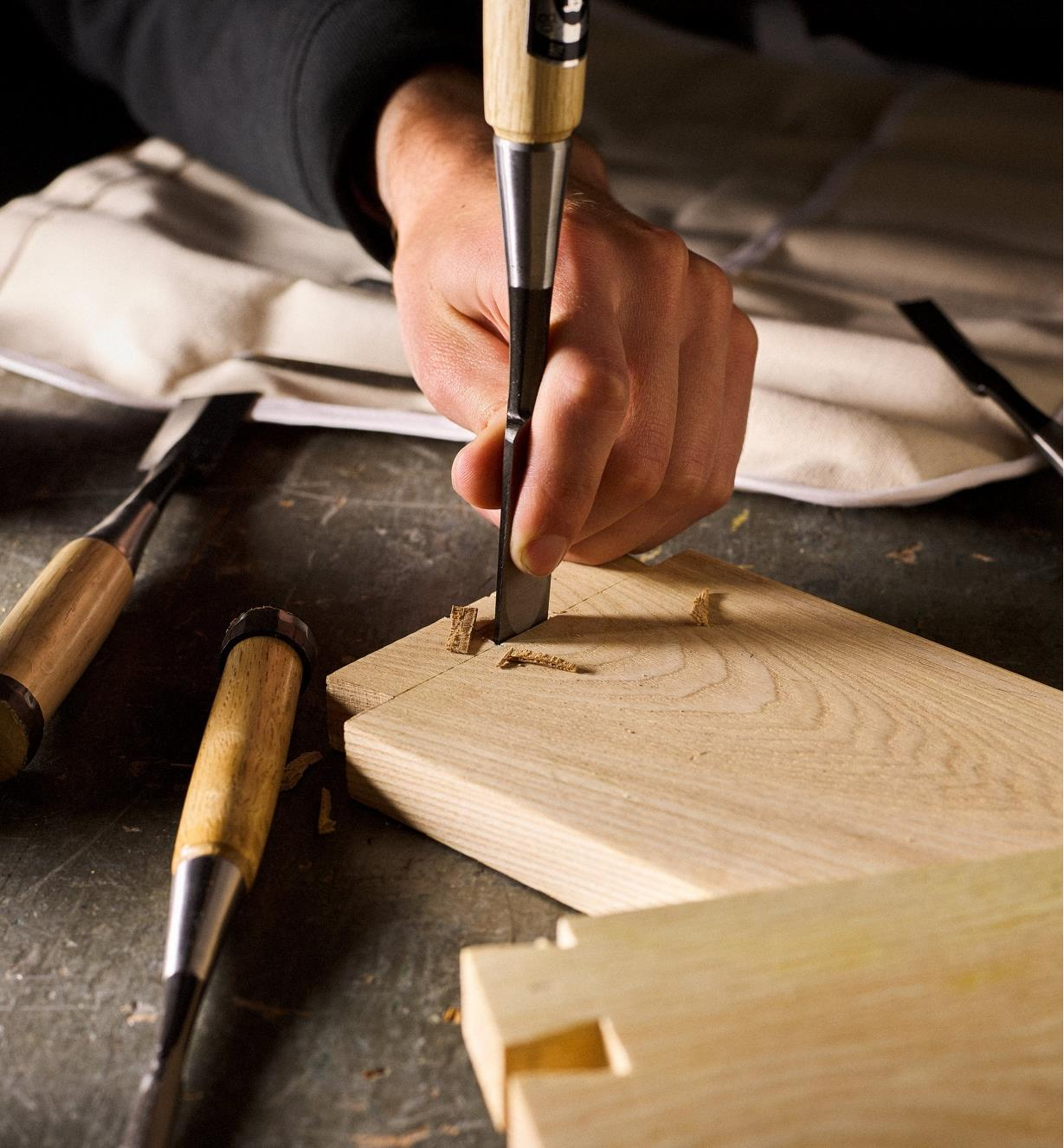 Using a Japanese dovetail chisel to chop out the waste between the pins of a dovetail joint