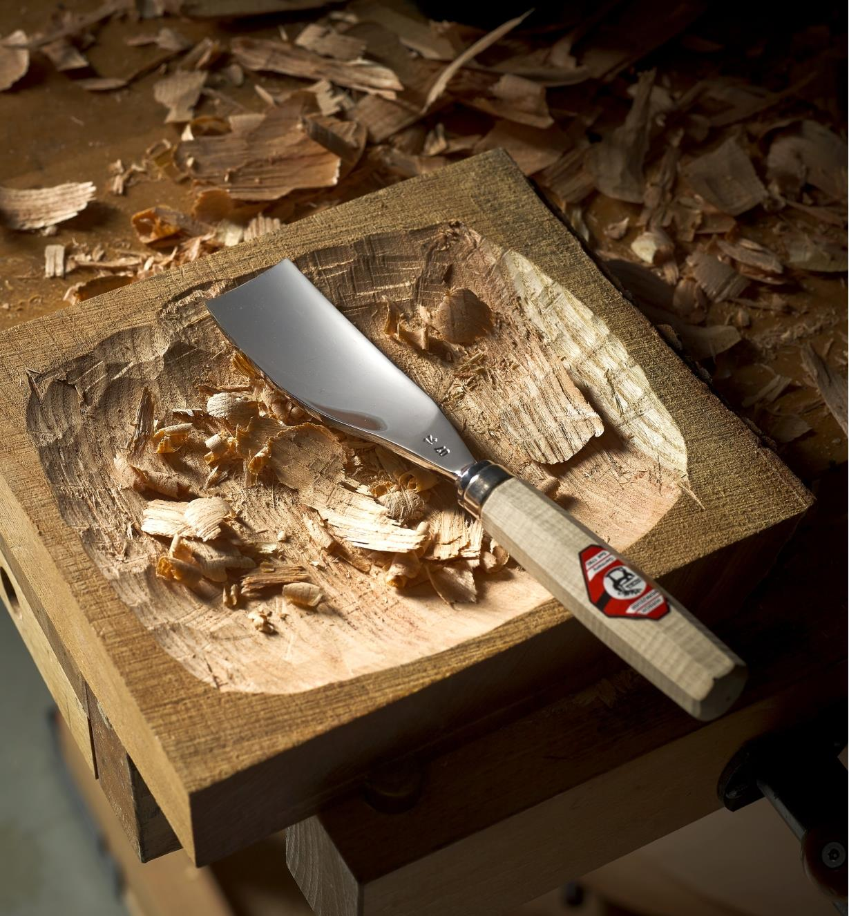 The Hirsch large #5 bent gouge lying on a shallow wooden bowl covered in shavings