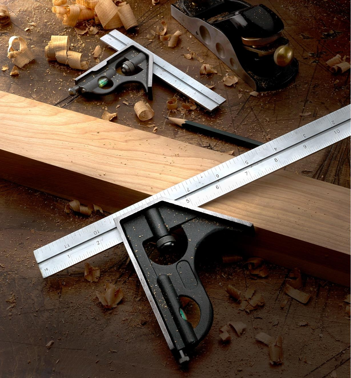"A 12"" combination square set on a piece of wooden stock, with a 6"" square and a block plane nearby"