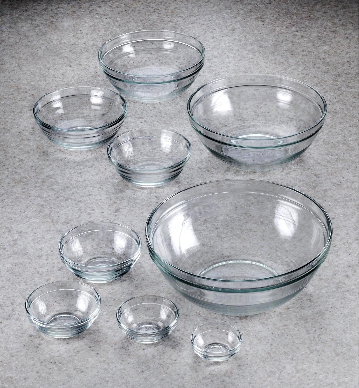 A set of nine Duralex glass bowls arranged on a countertop