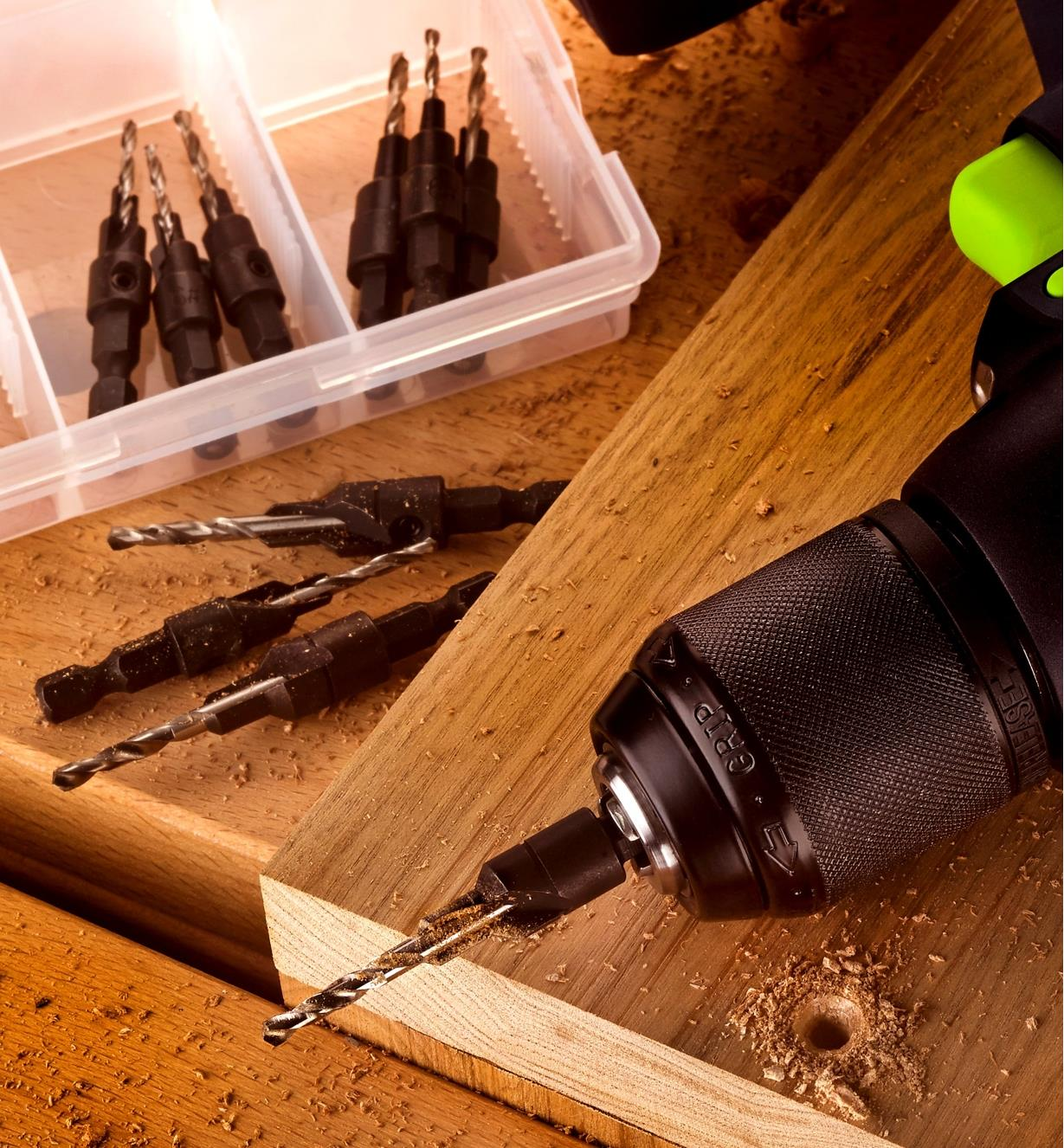 One of the pilot bits chucked in a drill, which lies beside a countersunk hole in a piece of wood