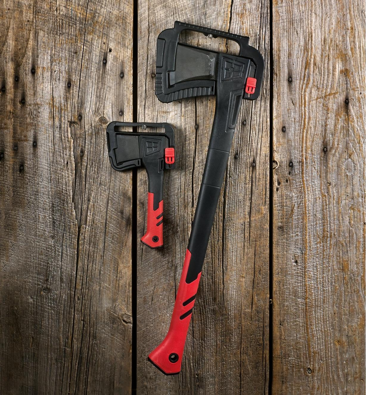 The splitting axe and hatchet held in their plastic storage brackets mounted on the wall of a shed