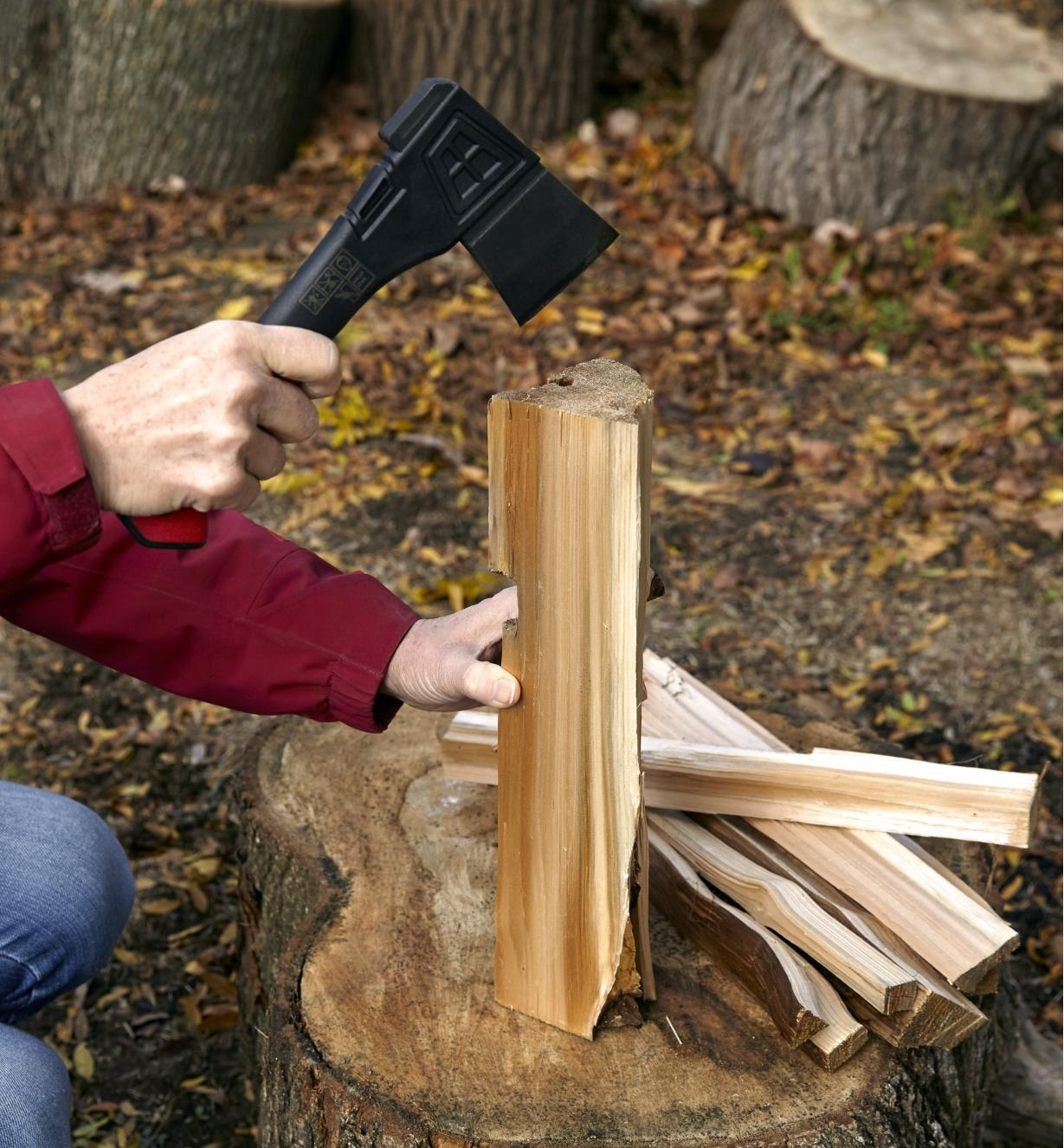 The hatchet being used to split a piece of firewood into kindling
