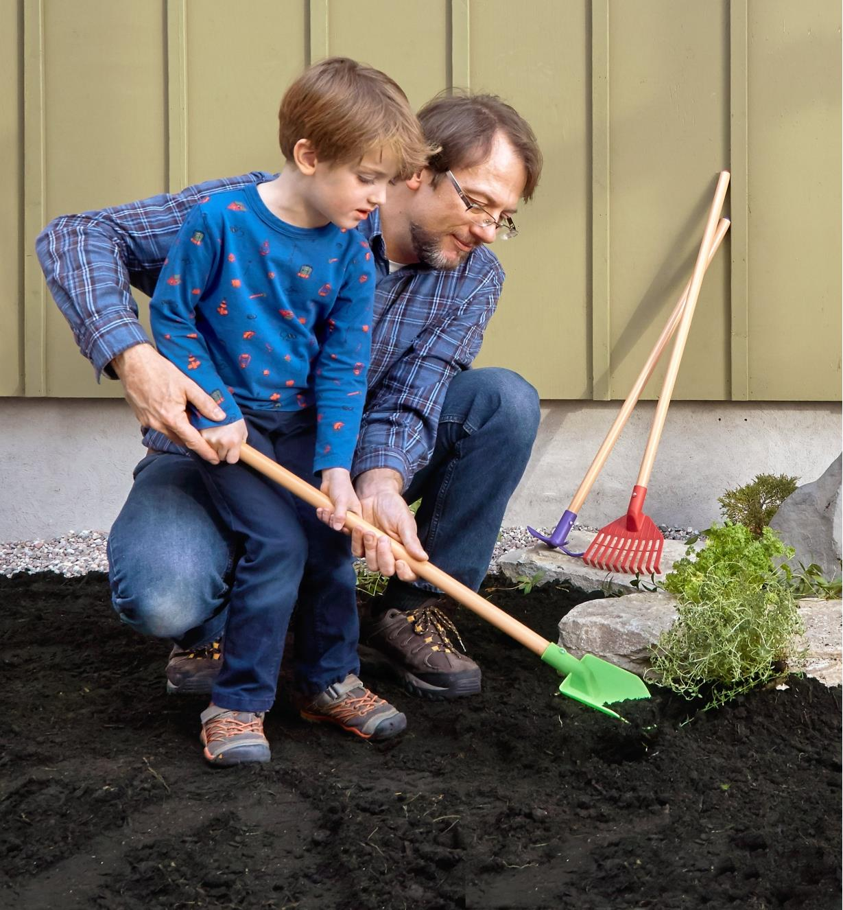 An adult helper with a child who is digging in the garden using the spade from the children's garden tools set