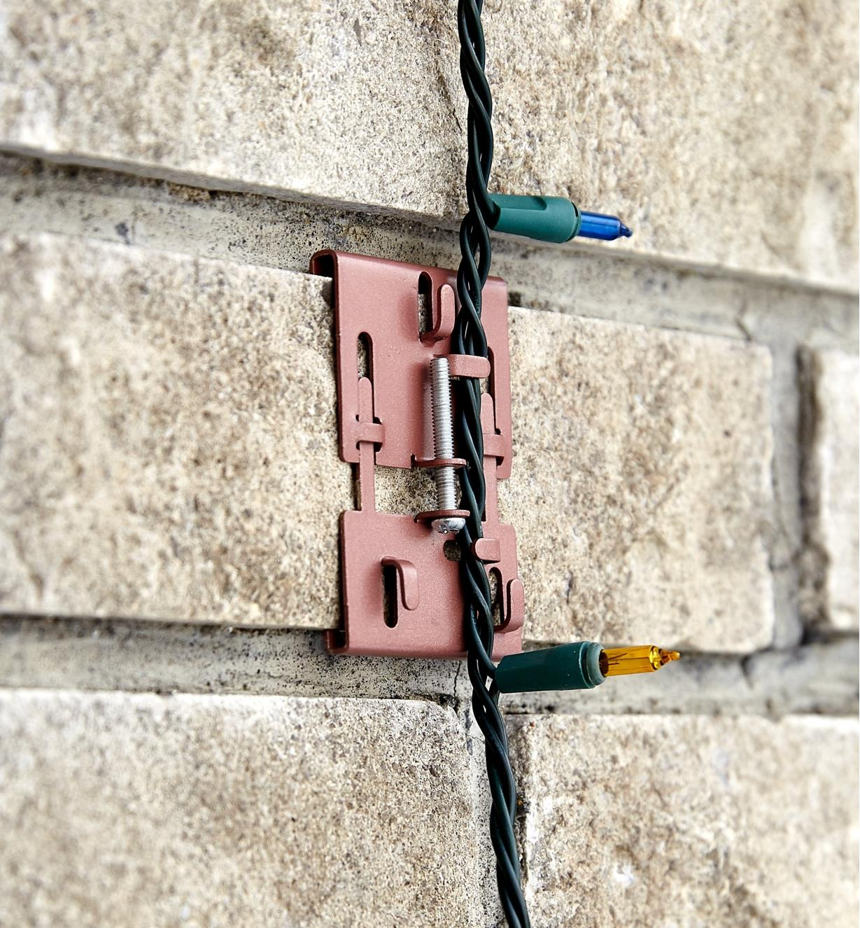 Brick clamp supporting a string of Christmas lights vertically on a brick wall