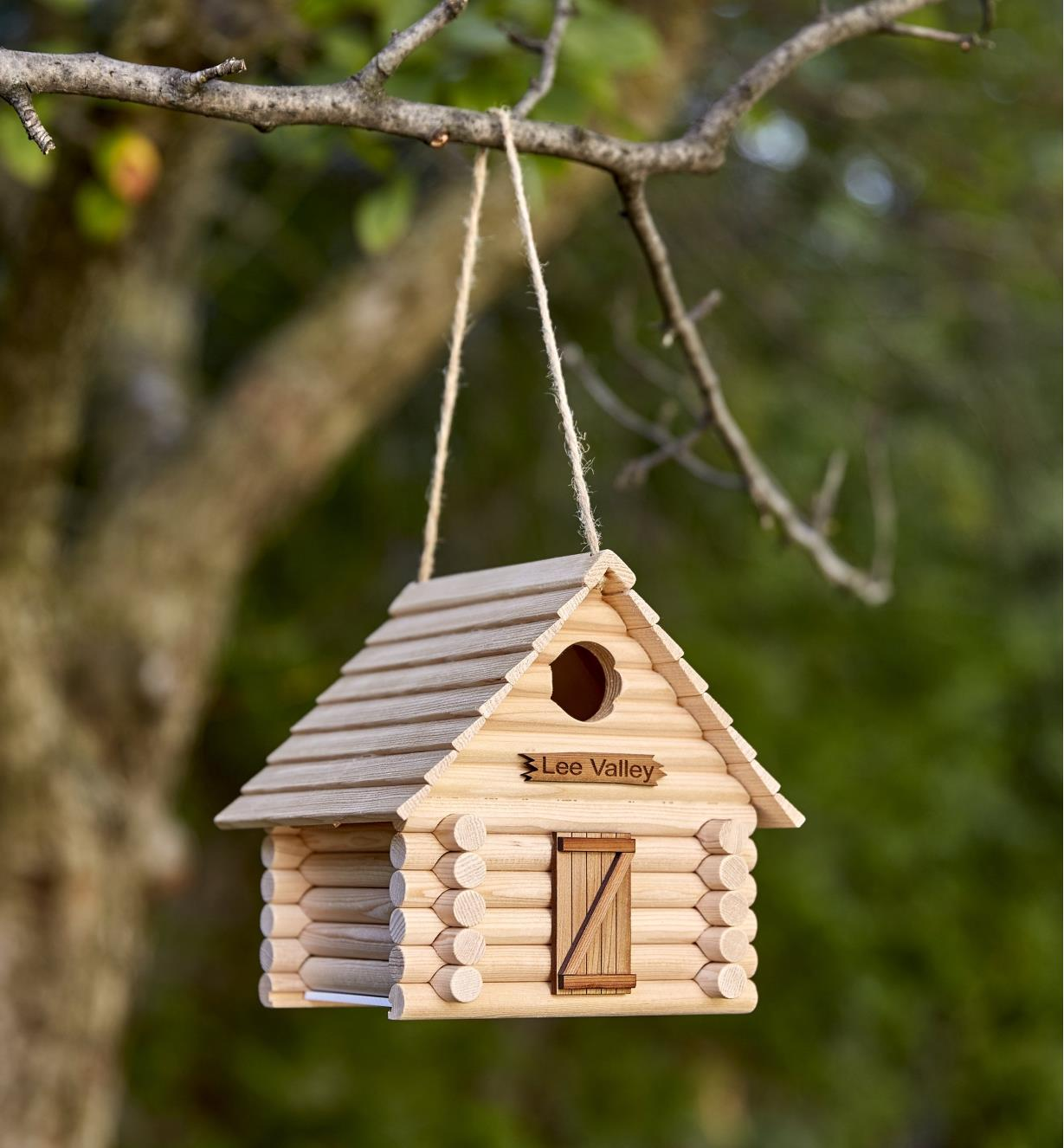 An assembled log cabin birdhouse hangs from a tree