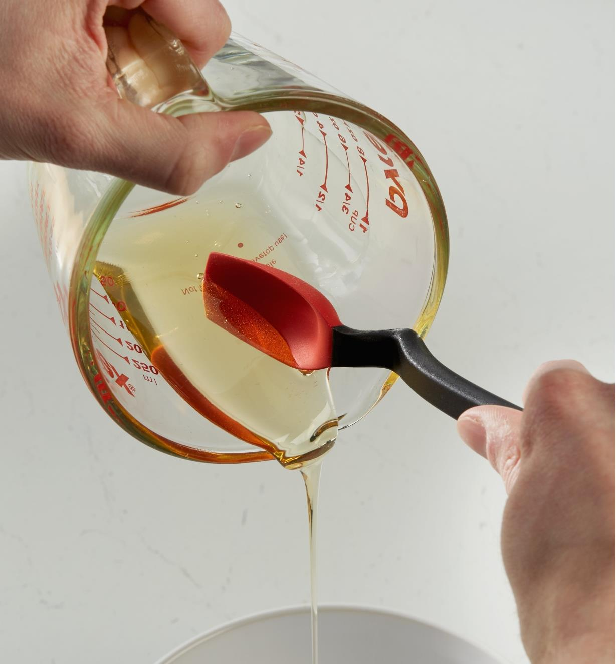 The mini spoon-spatula used to scrape liquid honey from a measuring cup