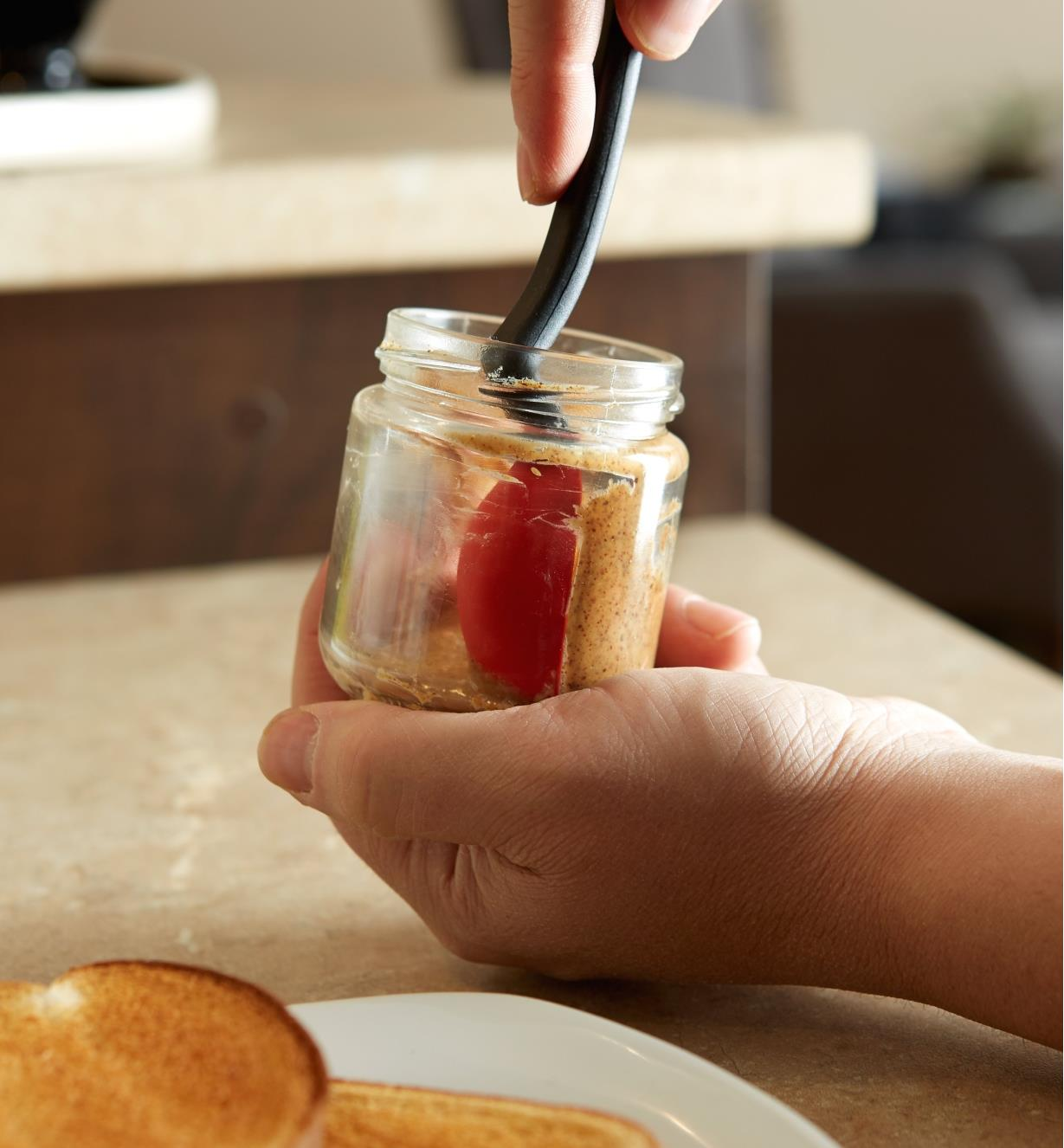 Using the mini spoon-spatula to remove the last bit of peanut butter from a small jar