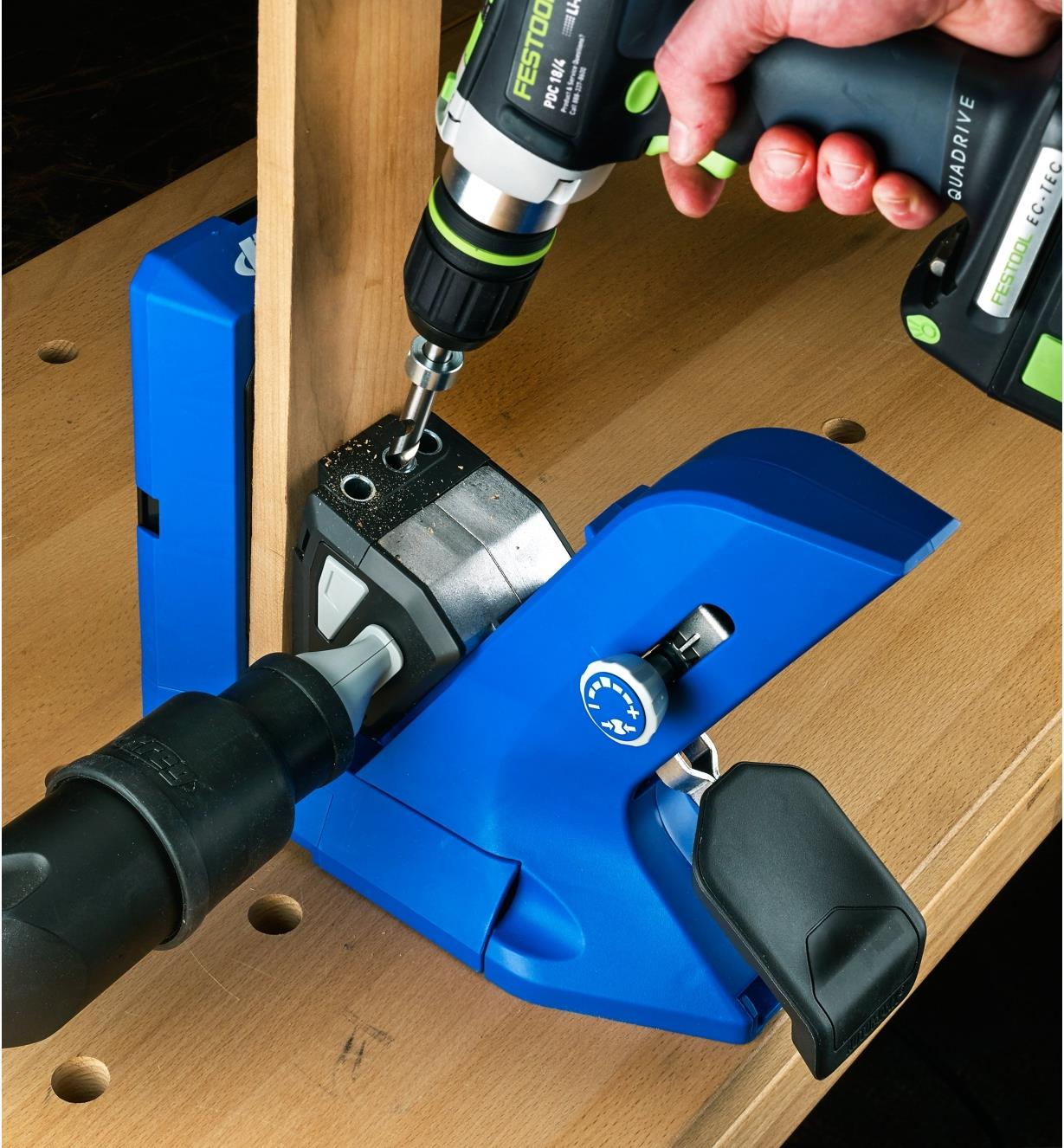 Drilling pocket holes using a Kreg 720 jig connected to a vacuum hose for debris clearance