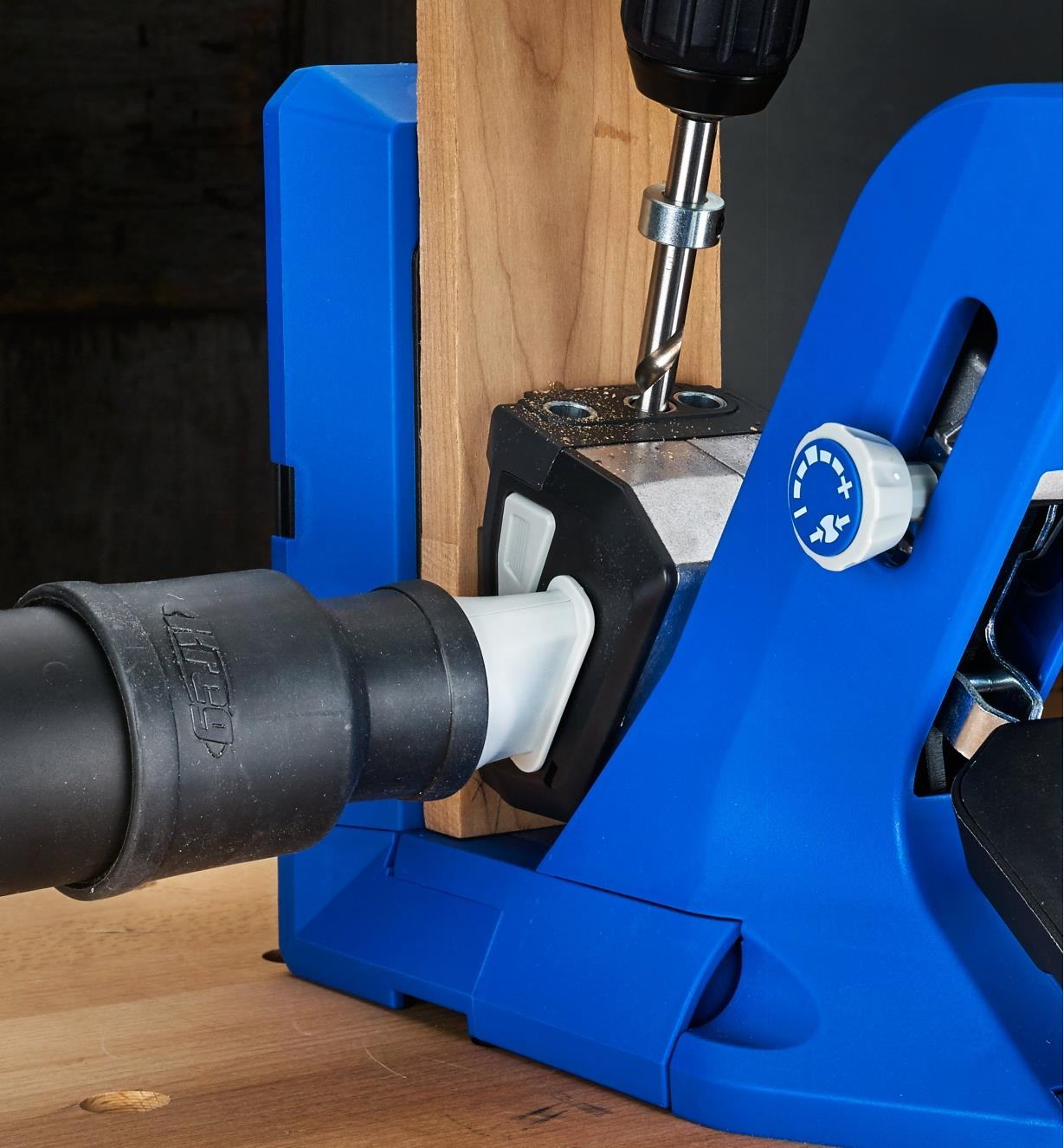 A close view of a Kreg 720 jig connected to a vacuum hose for debris clearance