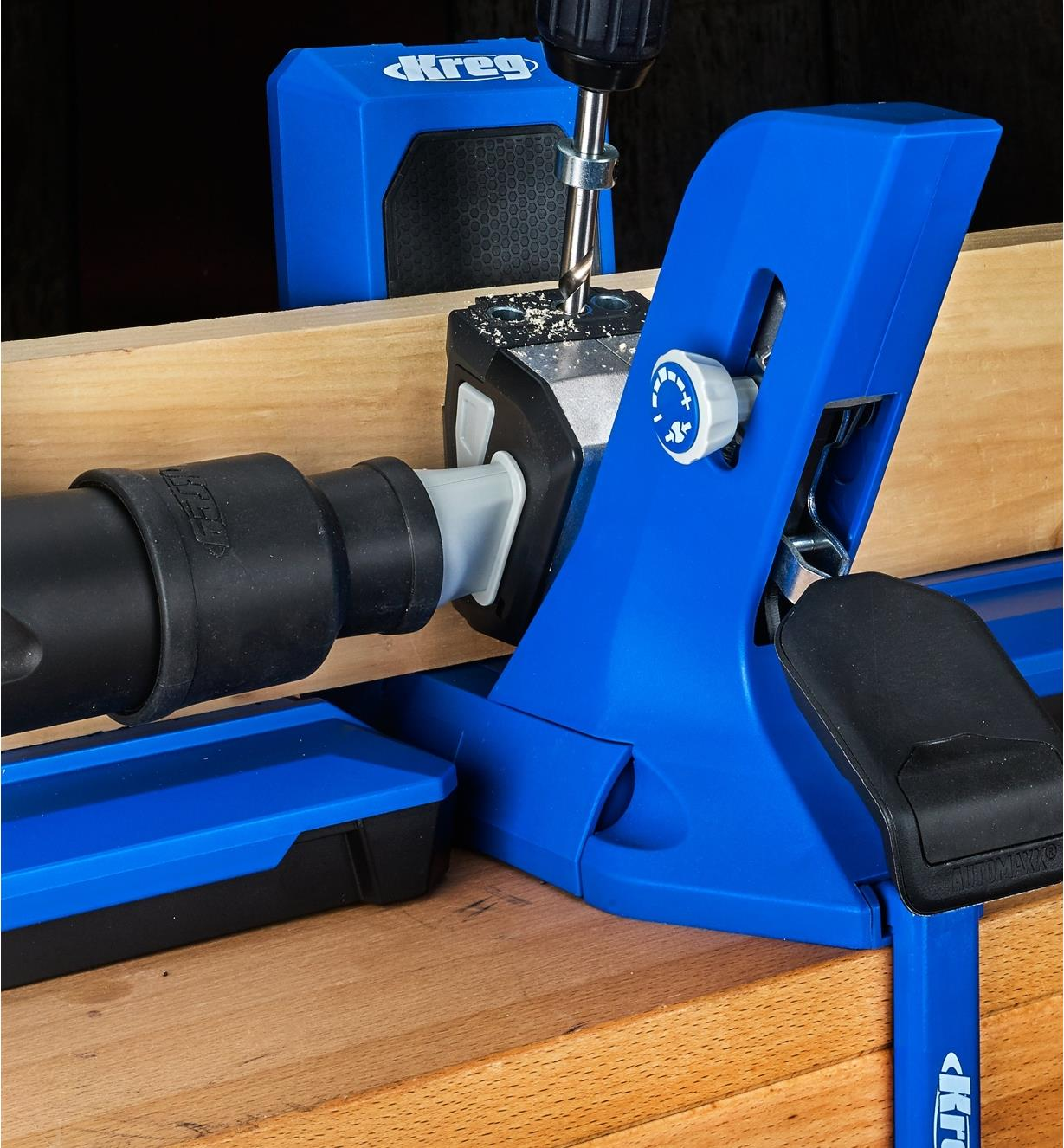 A close view of a Kreg 720 Pro jig connected to a vacuum hose for debris clearance