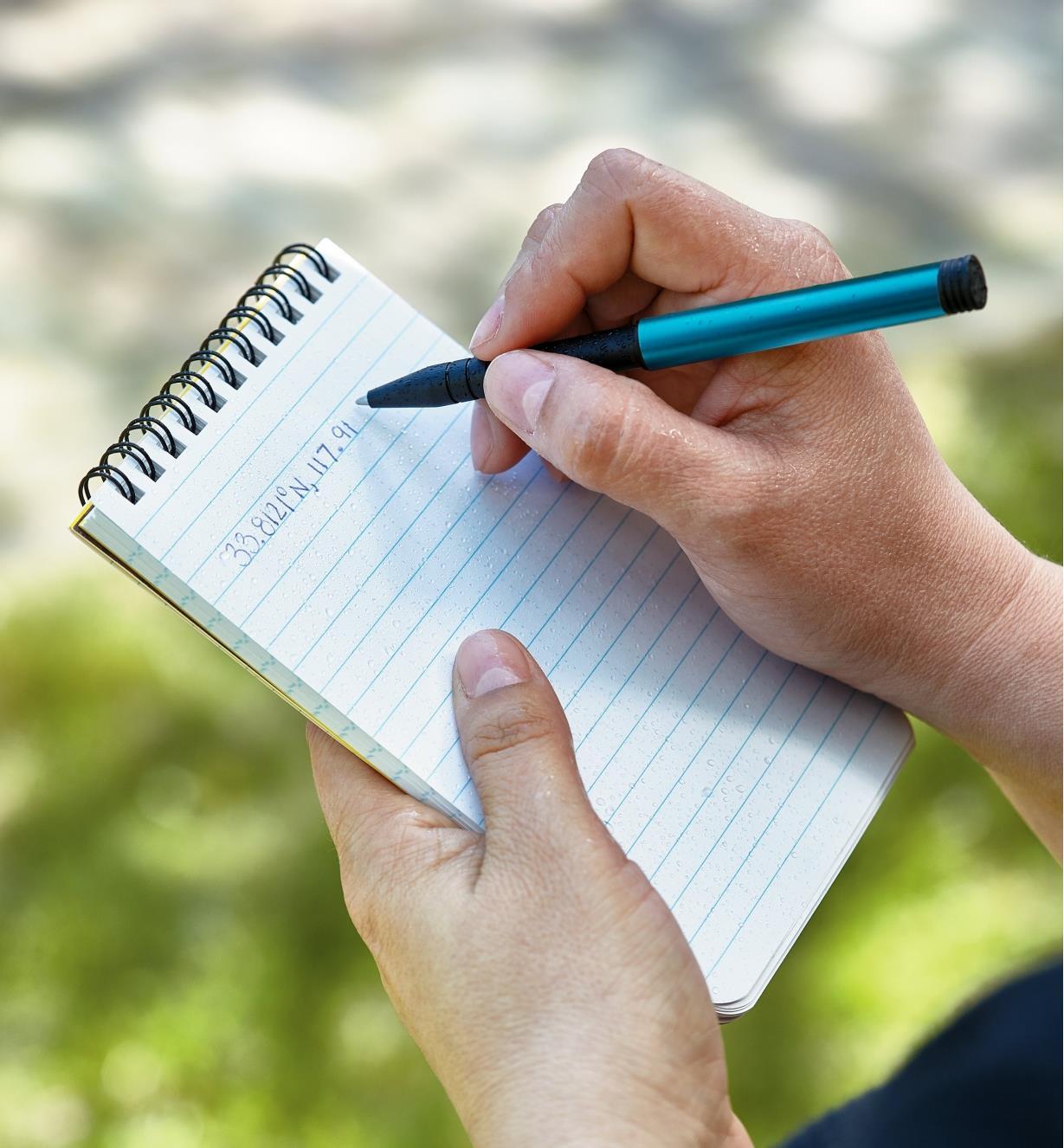 Personne écrivant dans un calepin avec le stylo d'aventurier Inka bleu
