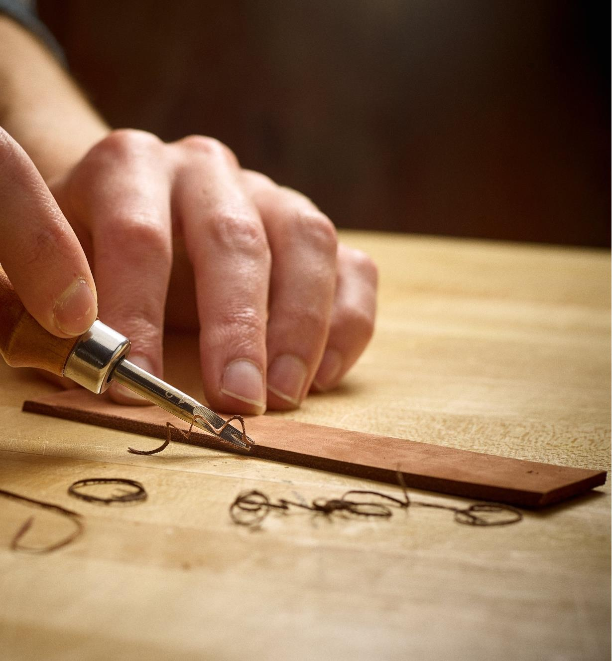 Using an edging tool to cut a radiused profile on a small piece of leather
