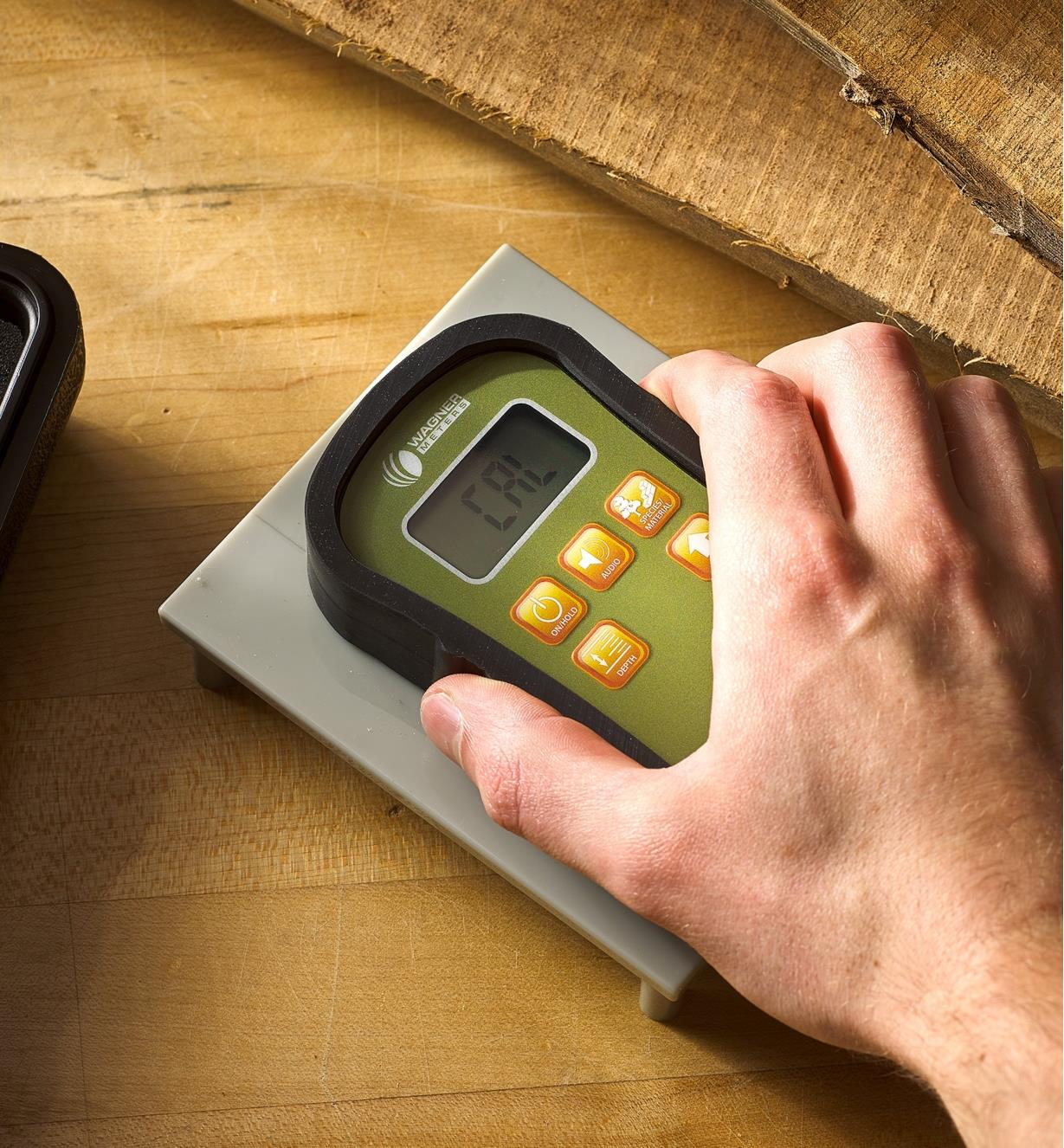A Wagner Orion 930 dual depth moisture meter is placed on a calibrator