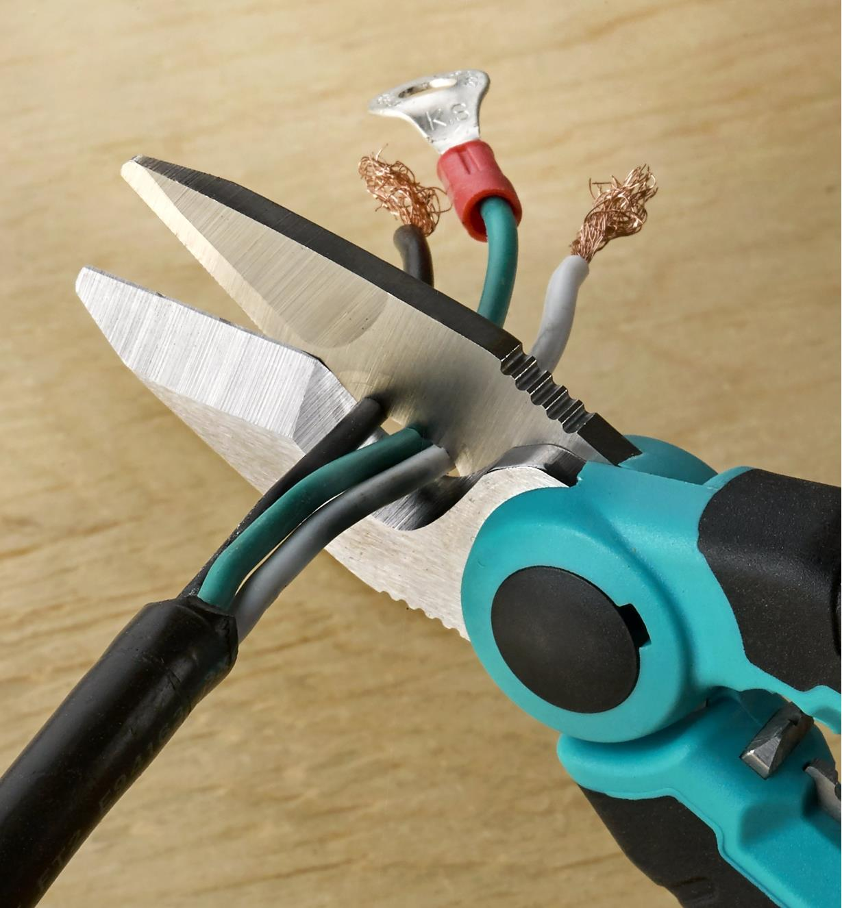A close view of the electrician scissors cutting three-strand conductor cable