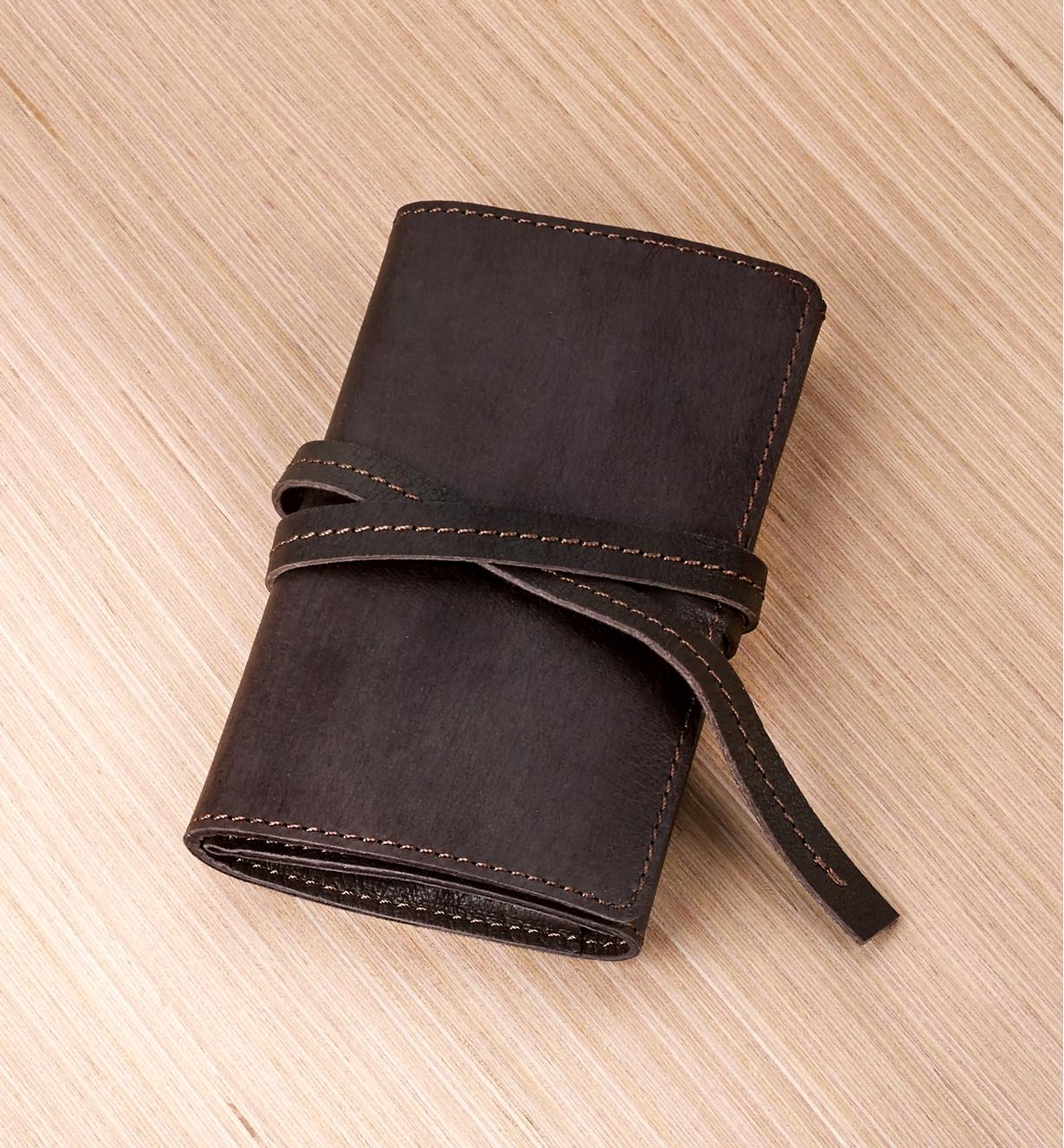 A leather cord wallet on a tabletop, cinched closed with its leather tie