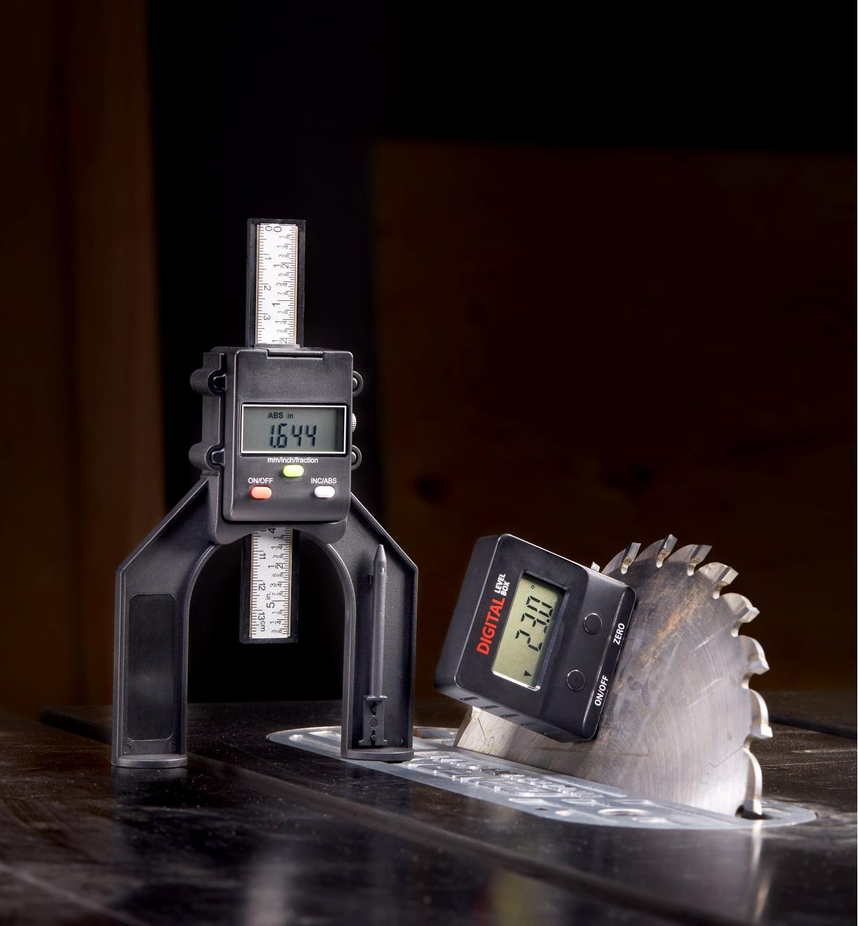 A digital height gauge beside a digital level box mounted magnetically to an angled table saw blade