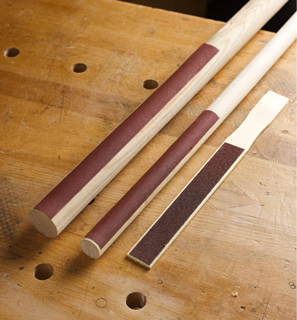 Cloth-backed sanding strips applied to sanding sticks for use on concave and flat surfaces