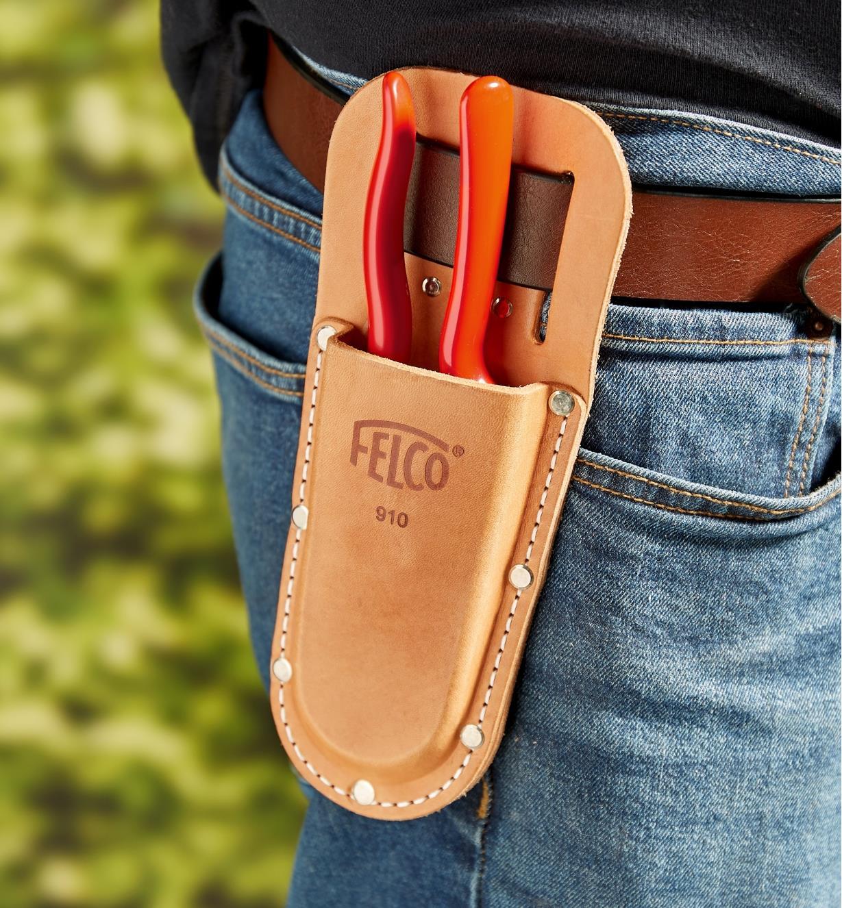 A gardener carries a Felco hand pruner in a pruner holster worn on the hip