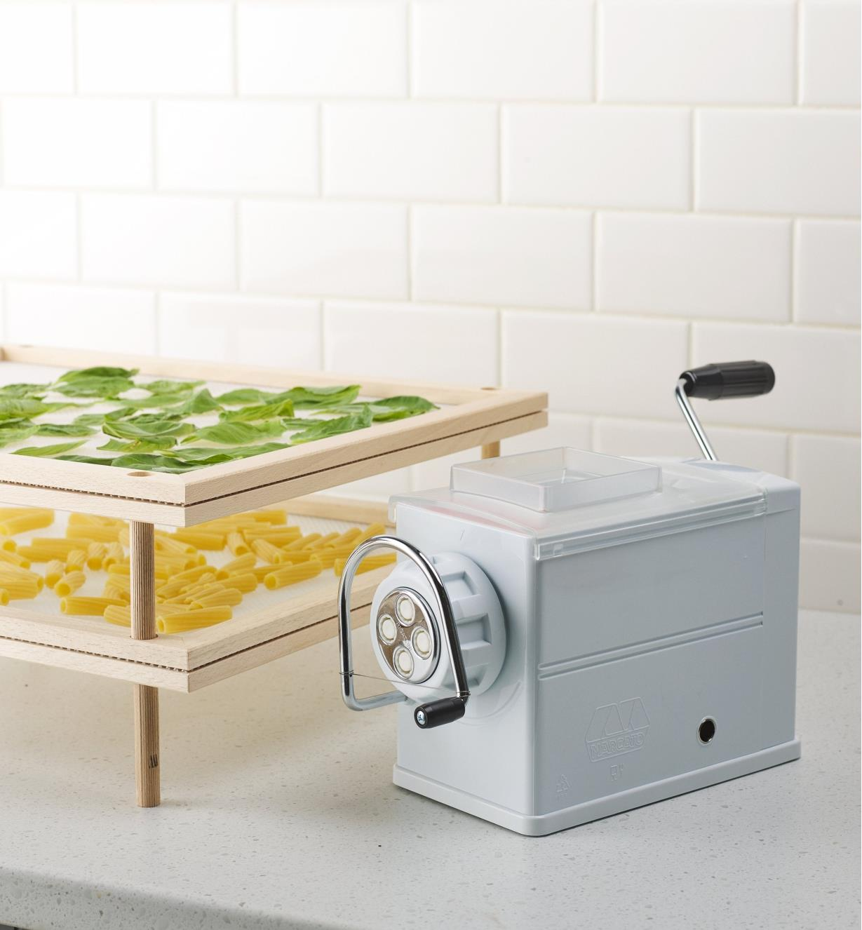 Marcato pasta extruder beside a pair of pasta and herb drying racks