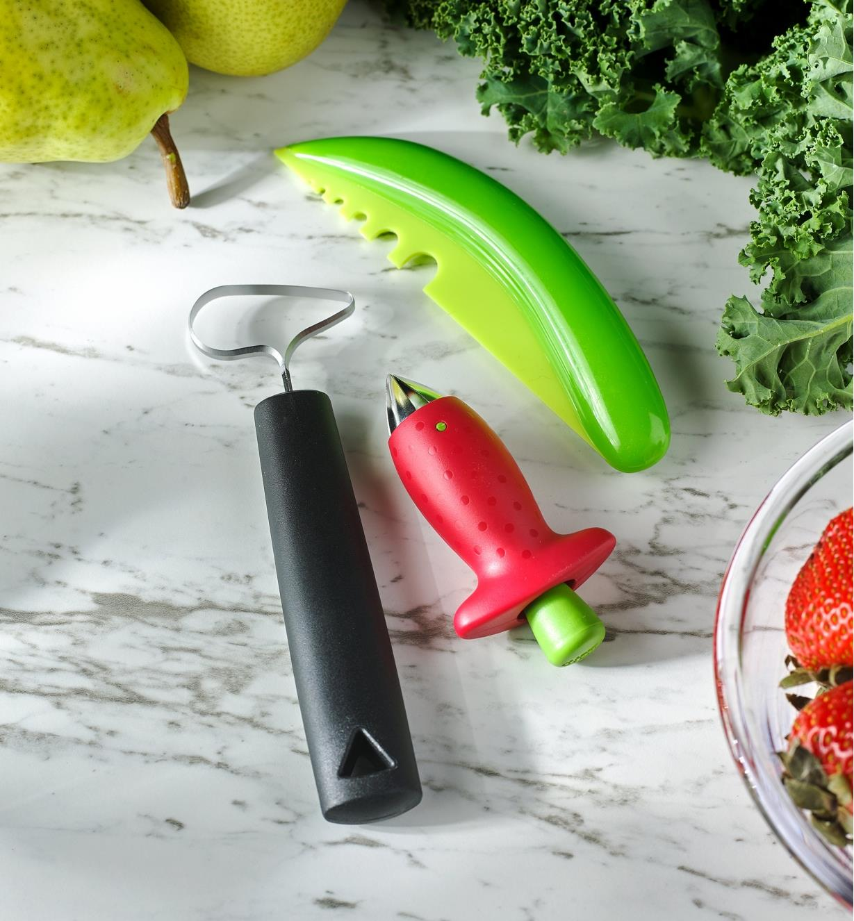 The fruit & vegetable corer, the herb stripper and the strawberry huller on a countertop